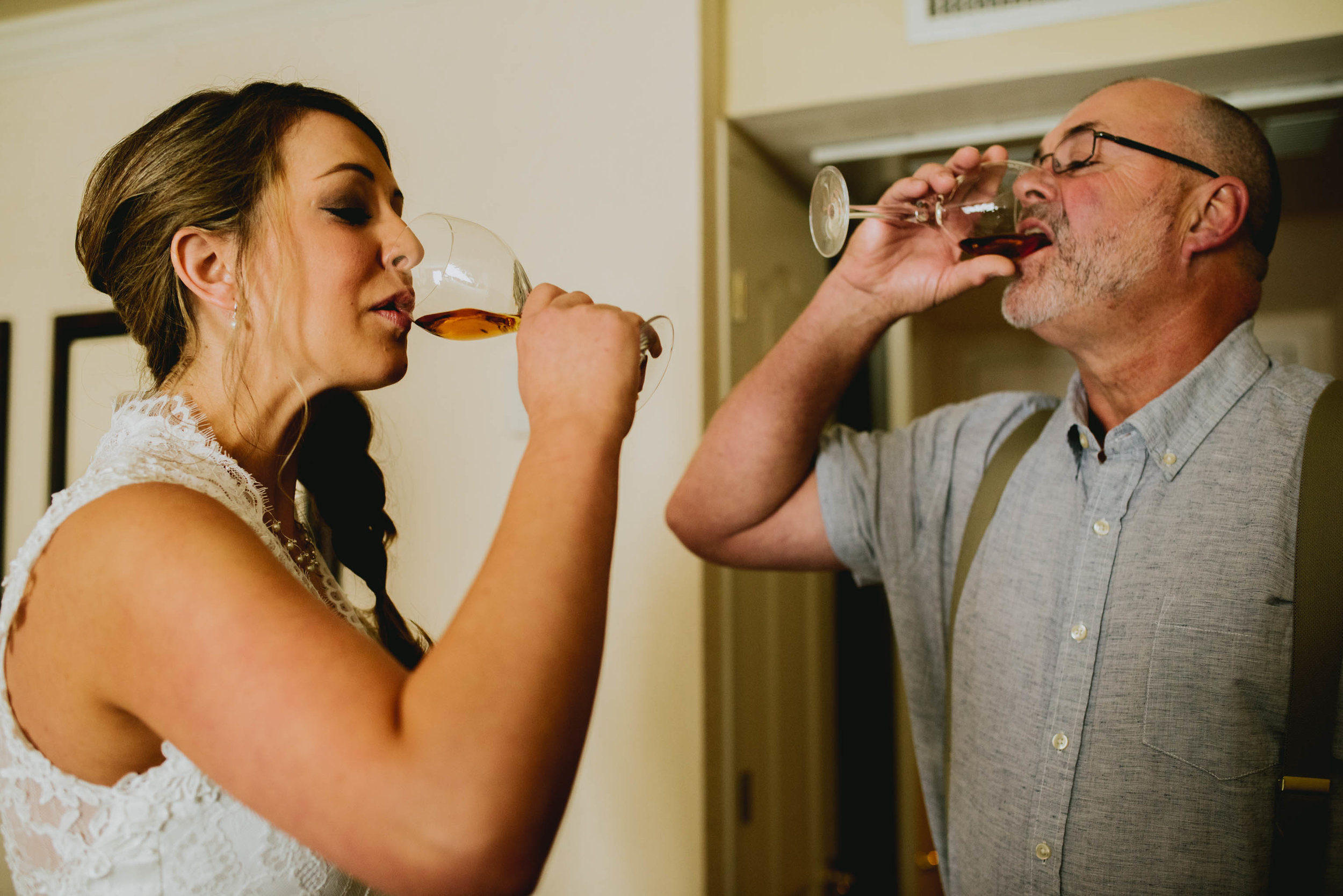 bride and father of the bride take a shot of whiskey