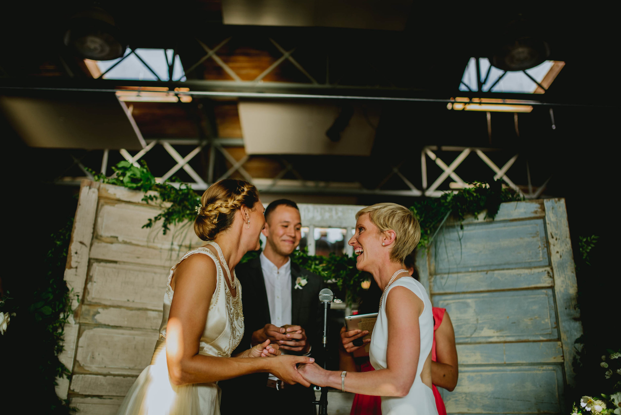 brides share a laugh with their officiants during their haw river ballroom wedding