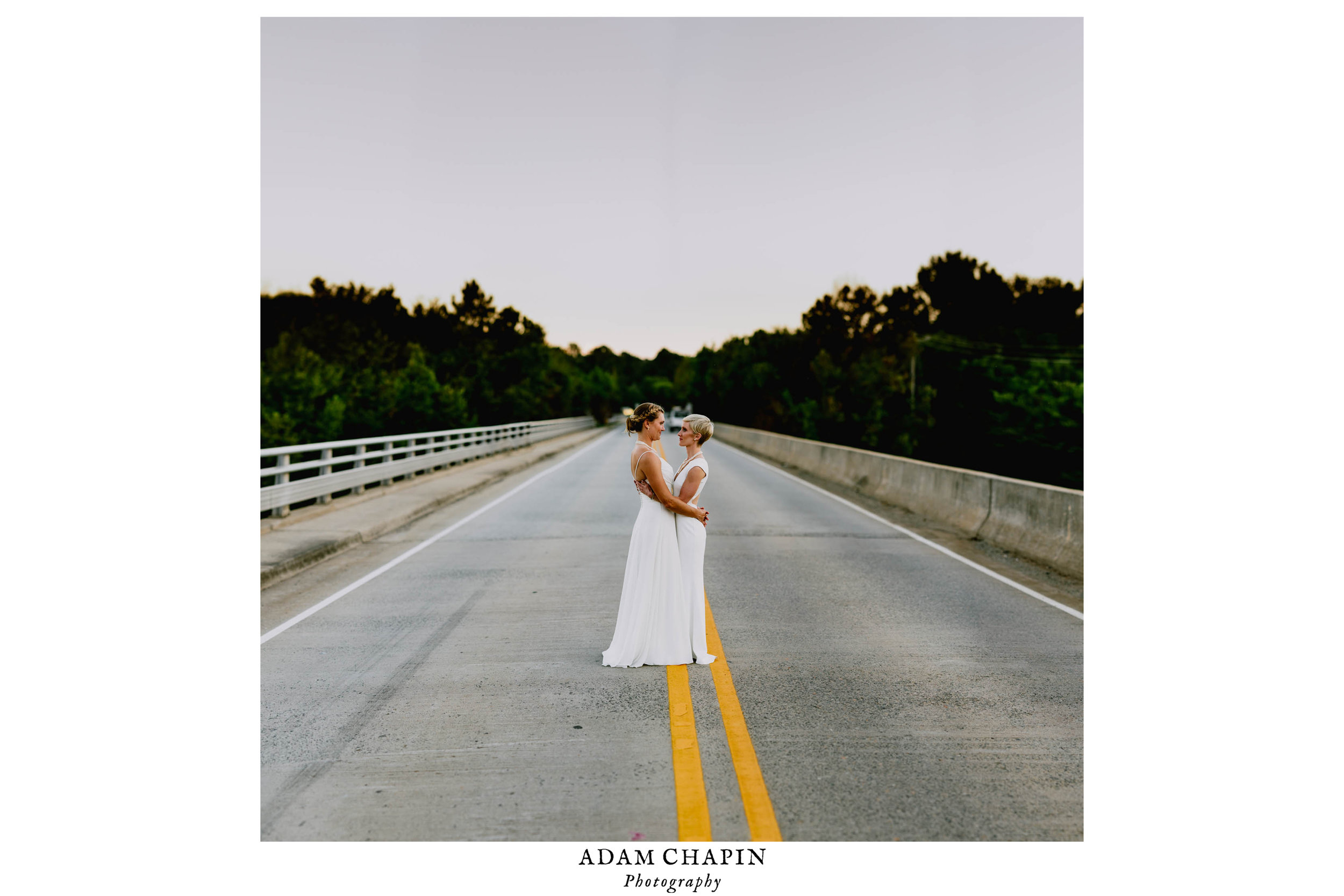 brides standing in the middle of the road on a bridge over the haw river in saxapahaw north carolina