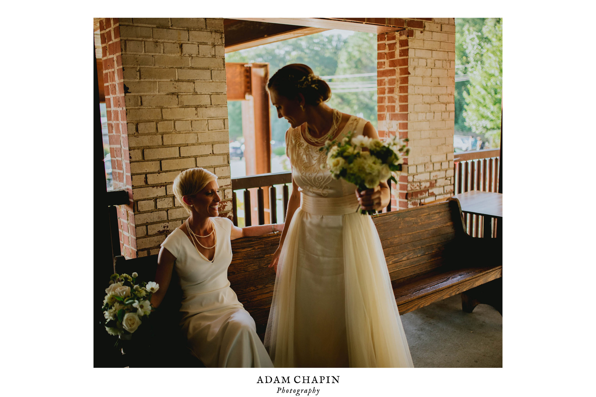 brides sharing a laugh just after their haw river ballroom wedding