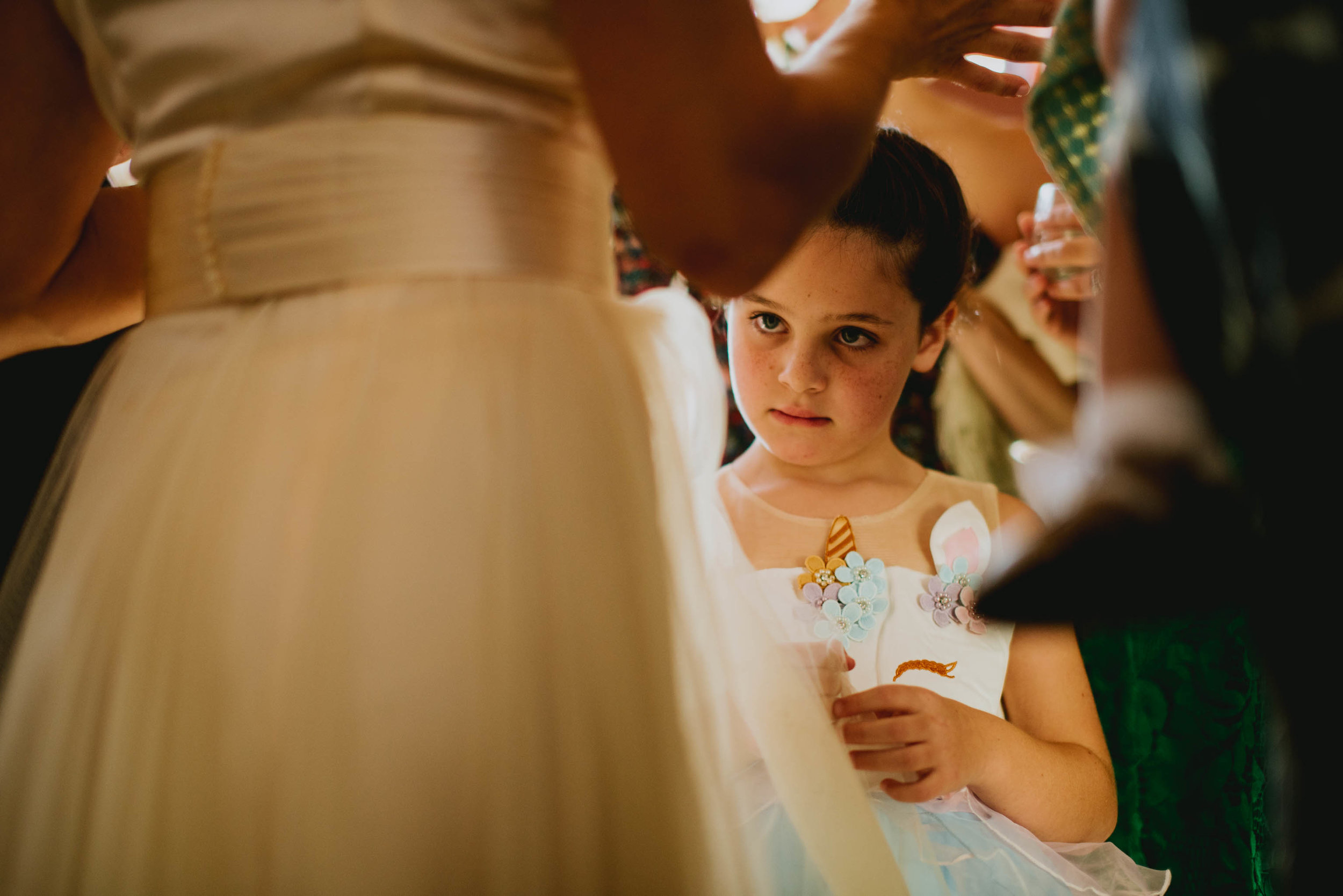 flower girl staring intently at the brides dress while the adults carry on conversation