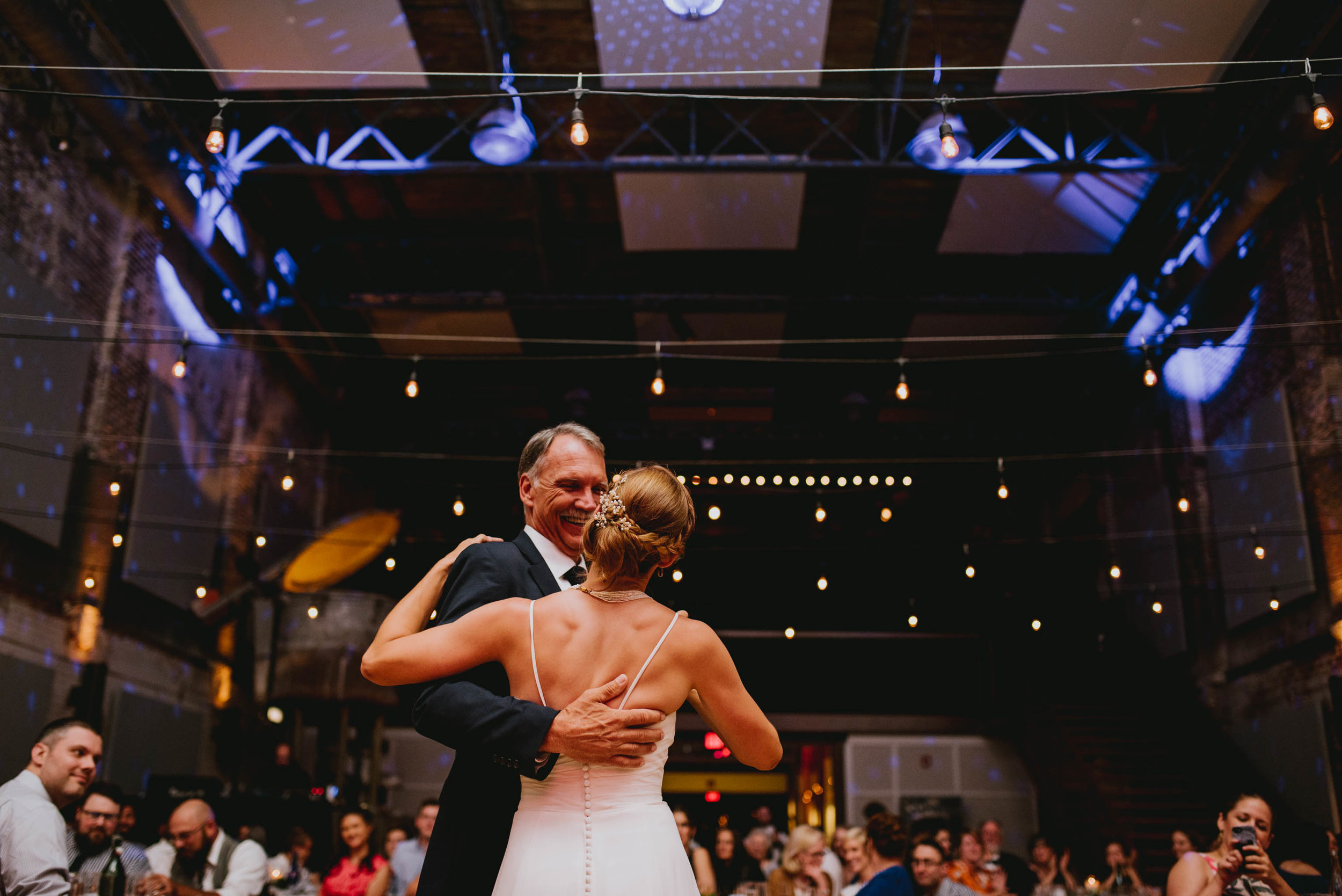 bride sharing in first dance with her father with the beautiful backdrop of the haw river ballroom