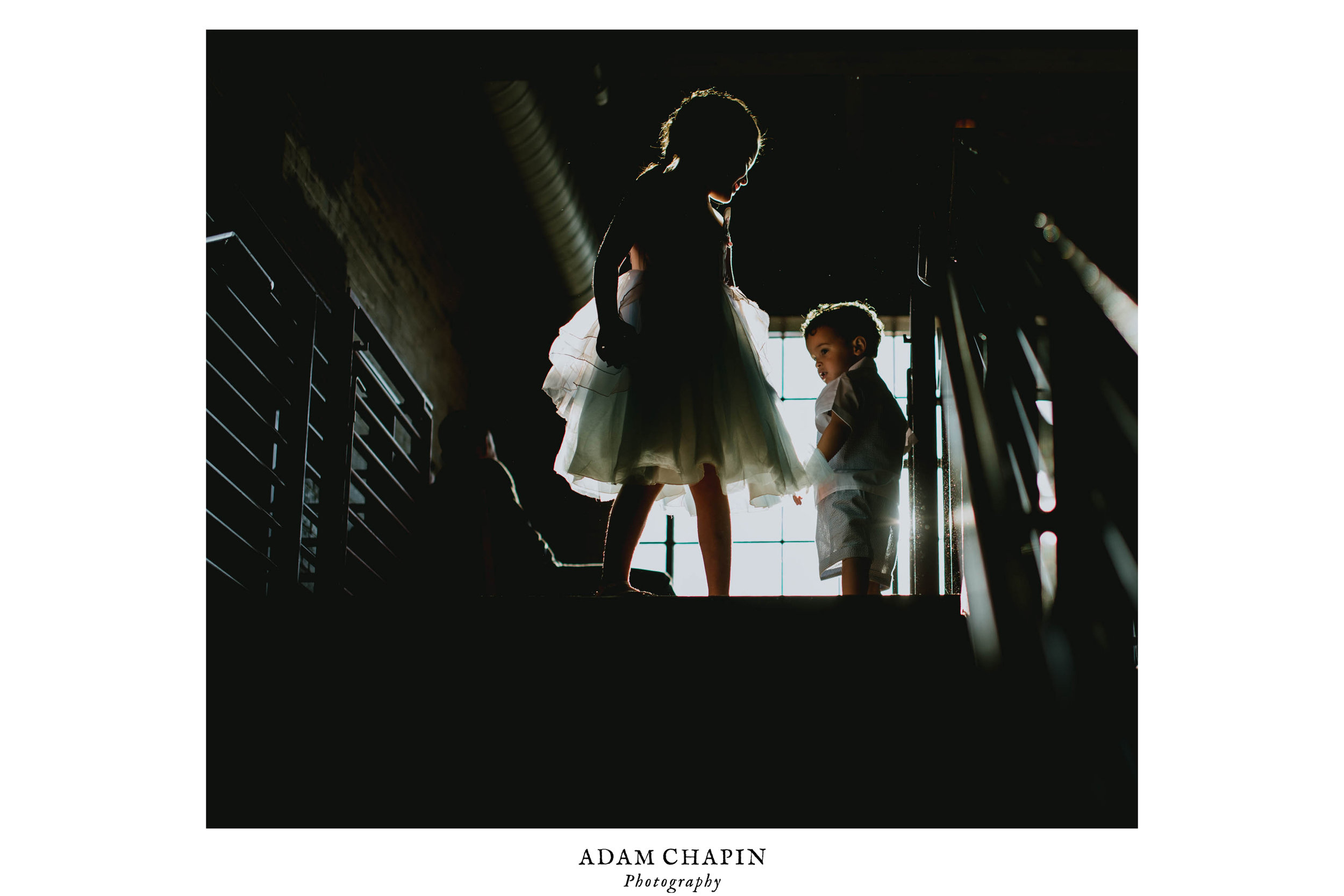 two children playing atop the stairs on the balcony of the haw river ballroom during the wedding reception