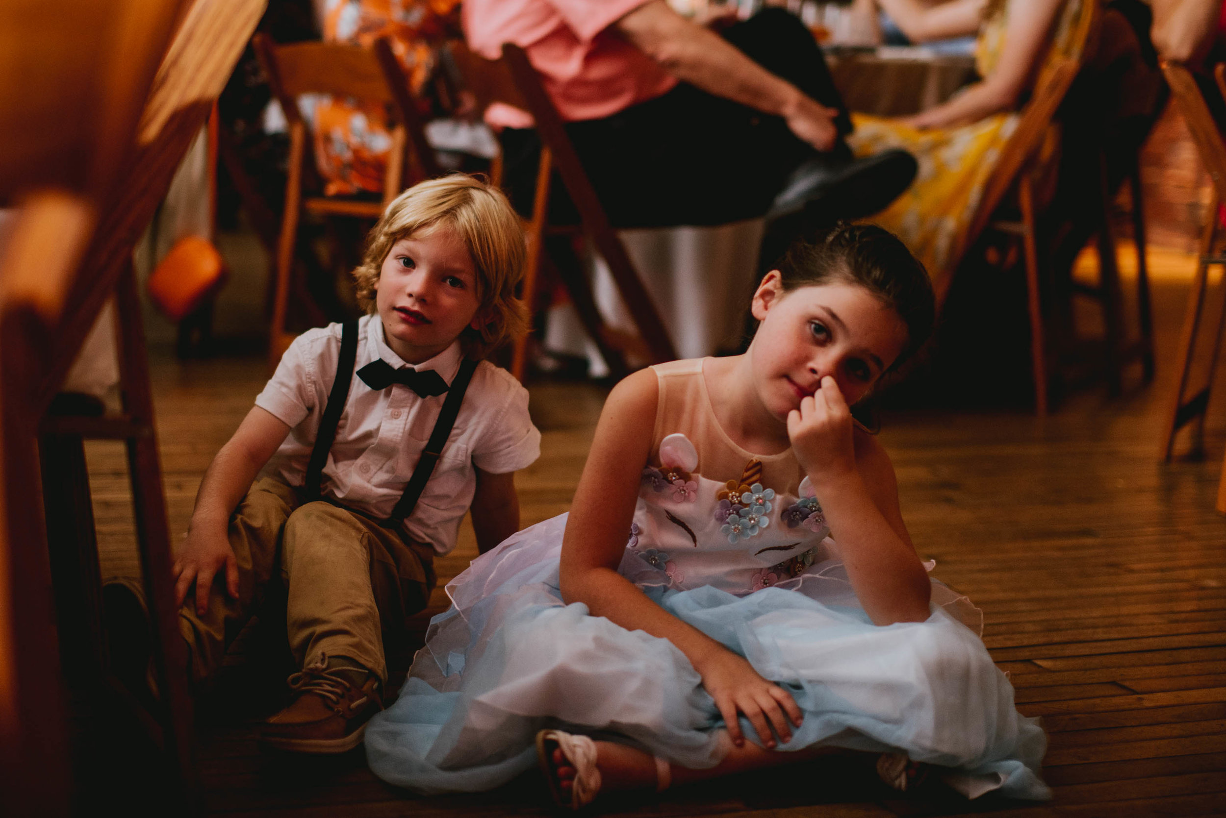 candid moment of kids sitting on the floor during toasts of this haw river ballroom wedding
