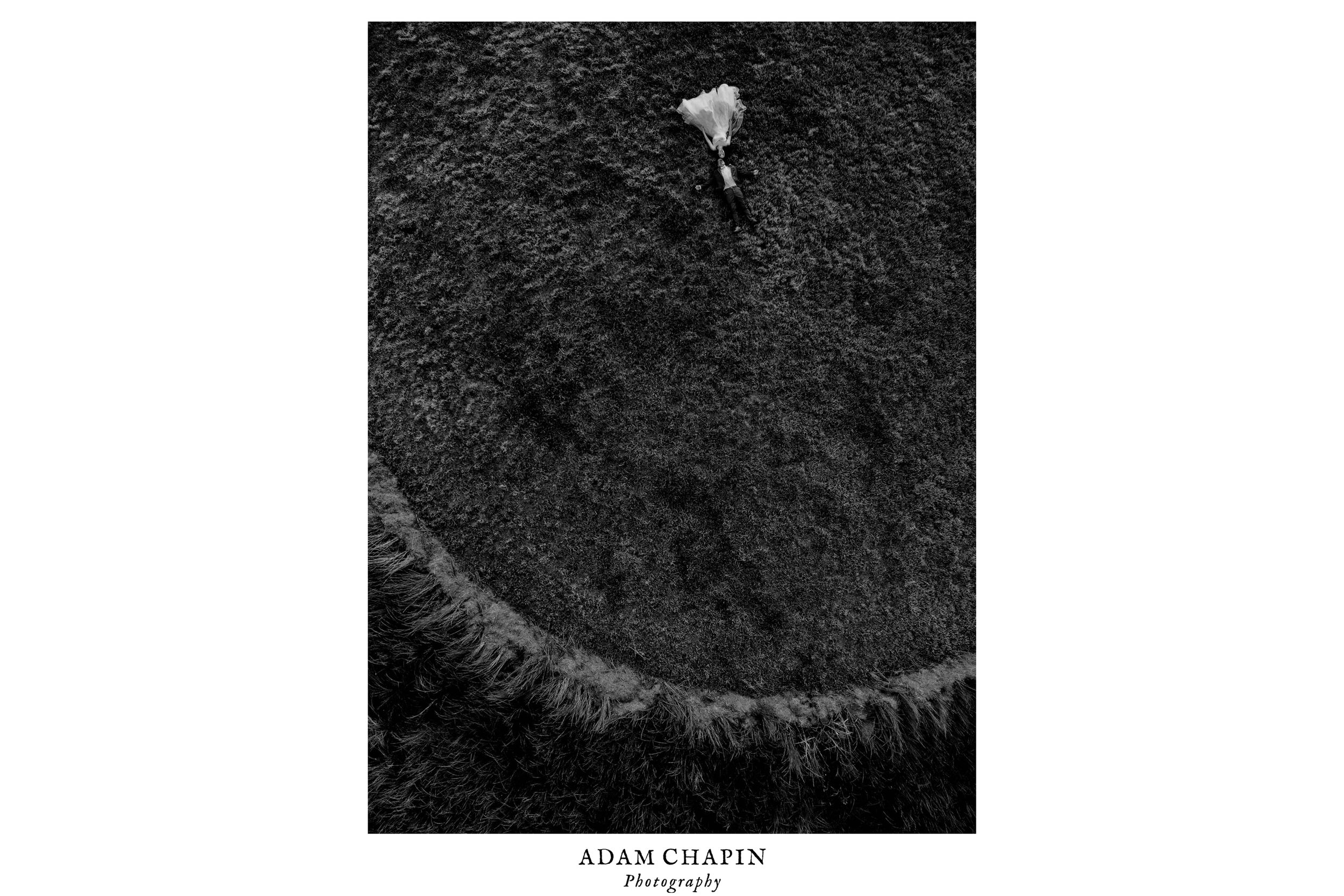 black and white drone photo of bride and groom laying down in a circular wheat field
