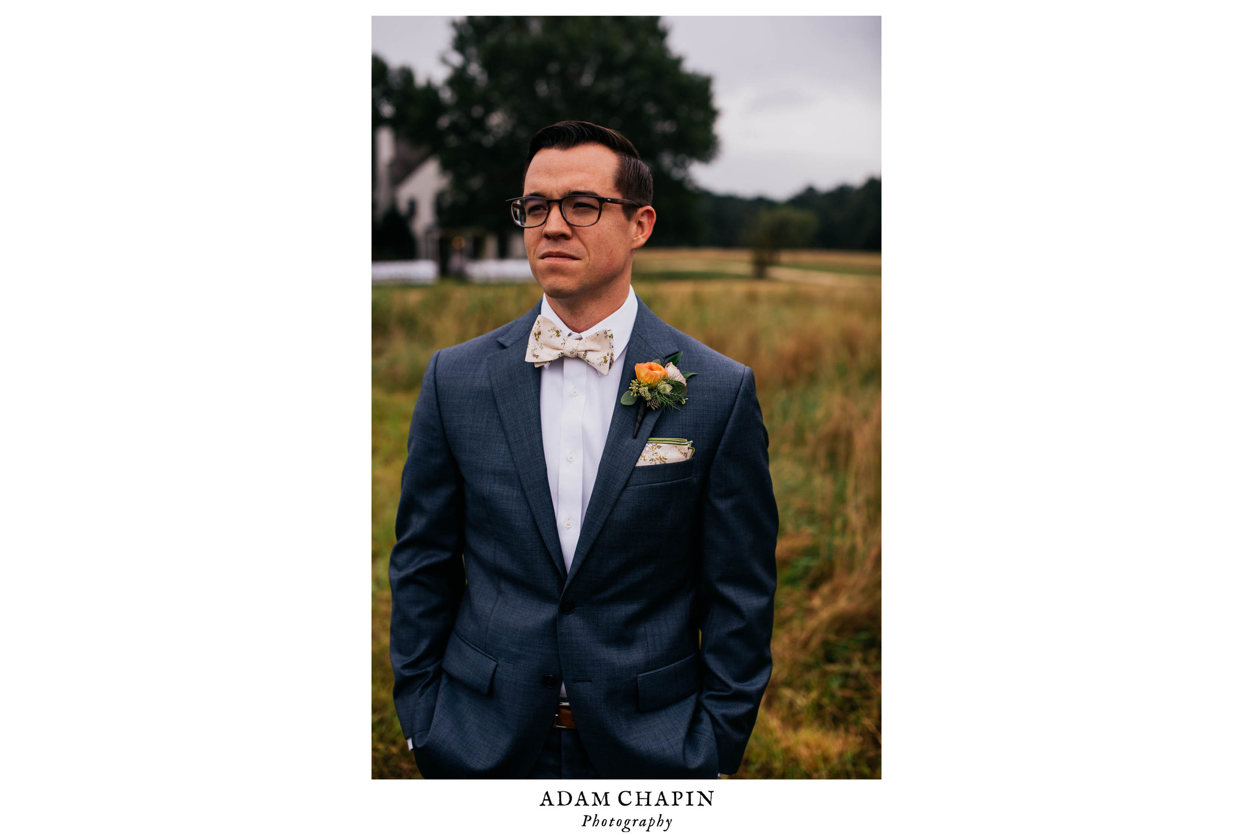 portrait of groom standing in a field before a first look with his bride before their wedding