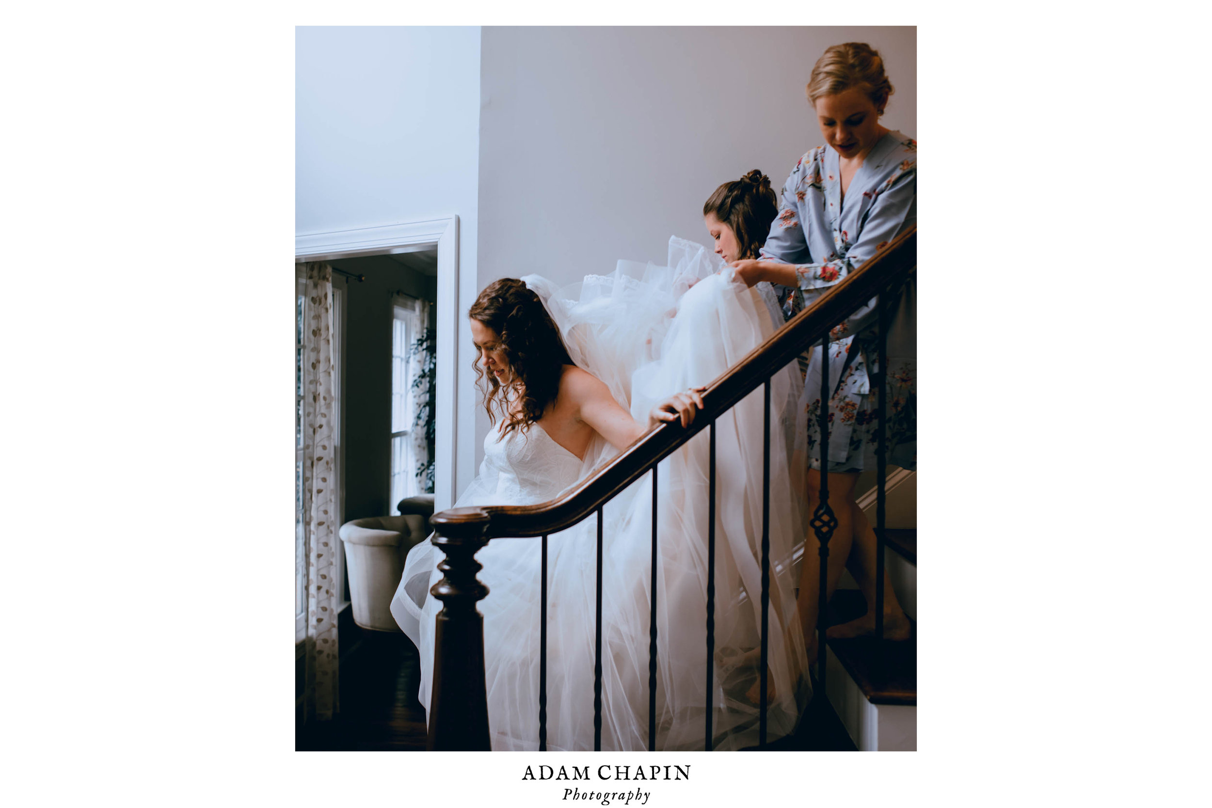 bride coming down the stairs with her bridesmaids carrying her veil and dress