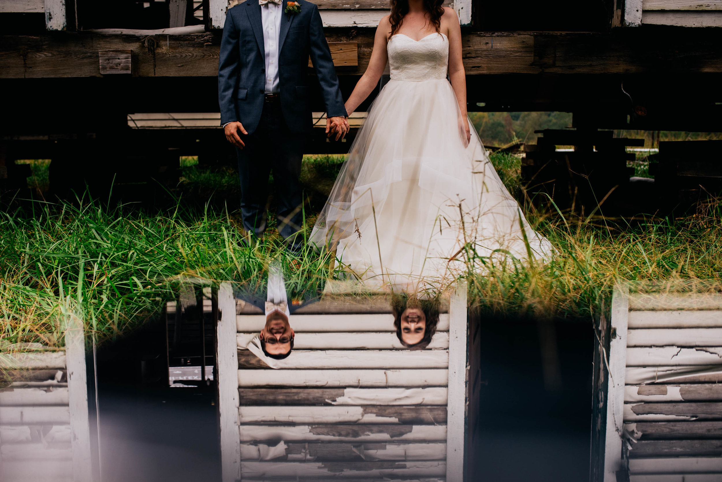 bride and groom as seen through a reflection on a piece of glass