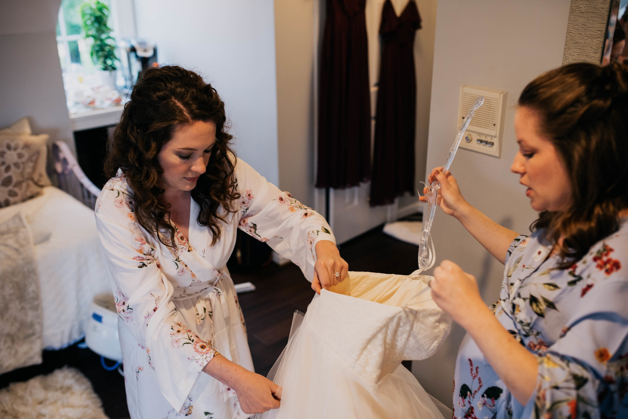 bride getting ready to get into her dress with the help of one of her bridesmaids