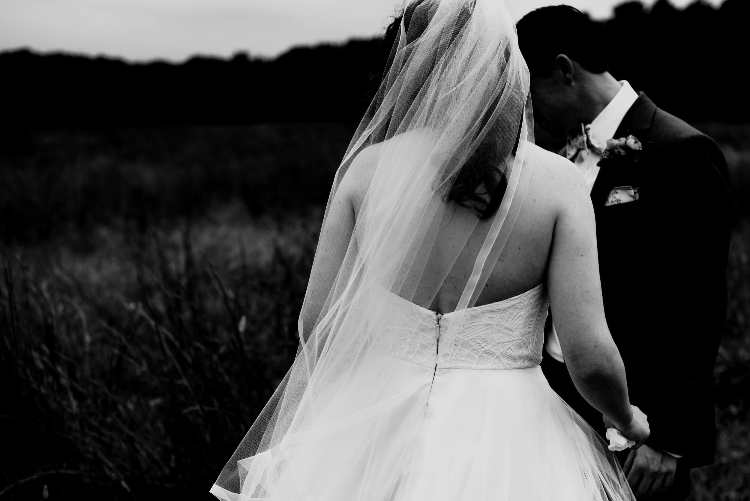 black and white photo of the brides veil in the wind taken from behind the bride