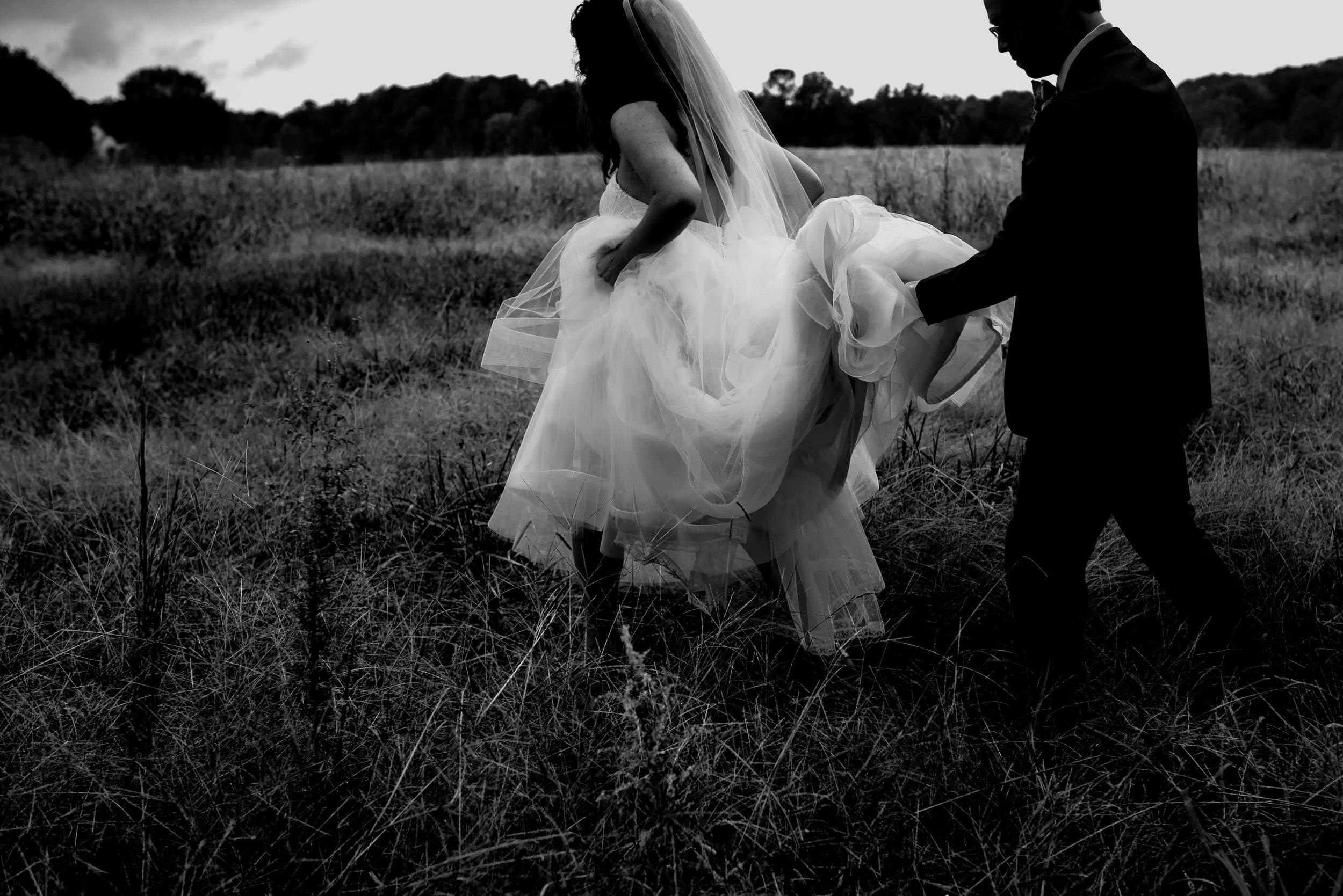 black and white photo of bride and groom walking out of the field during their wedding day