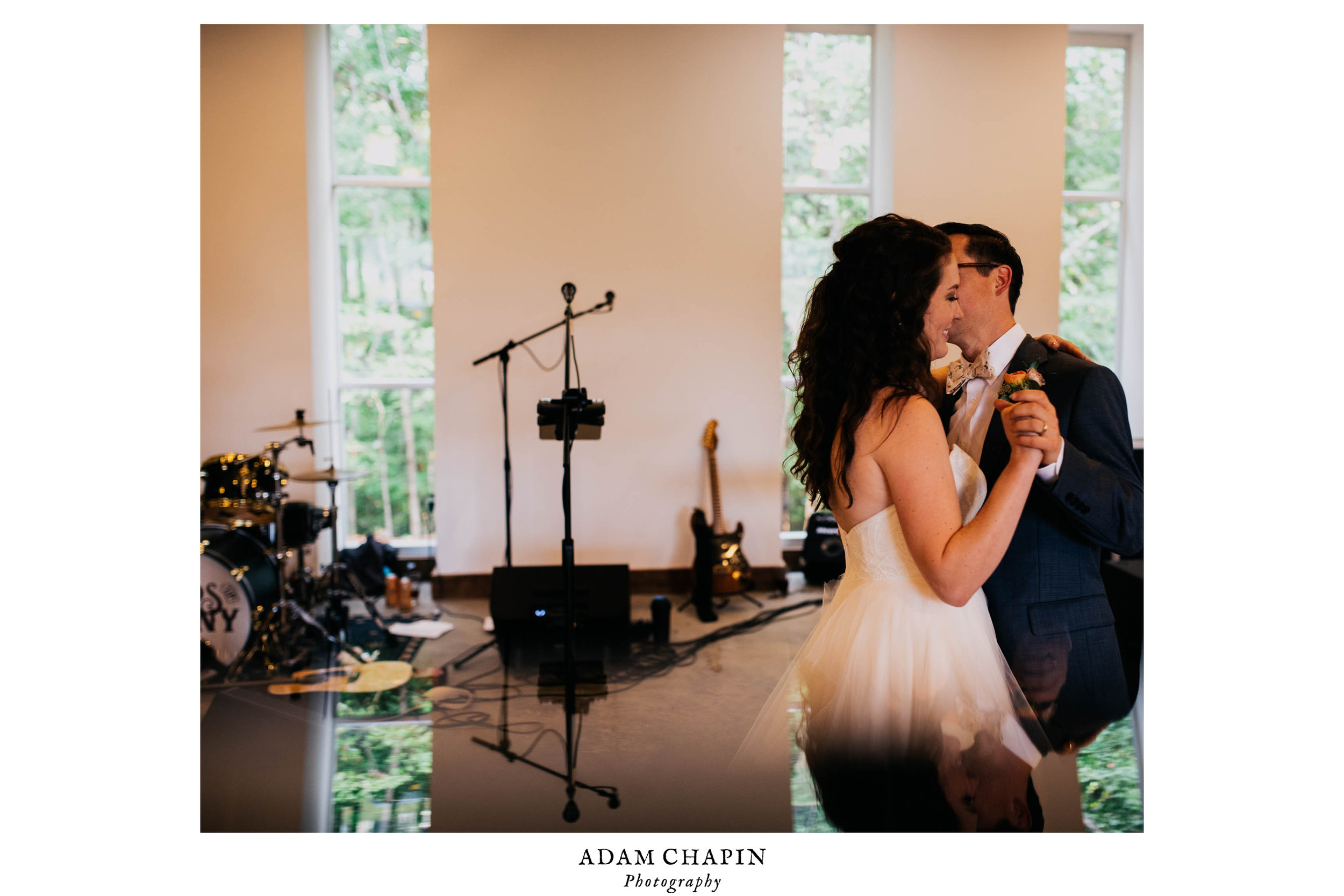 bride and groom enjoying their first dance and a kiss as seen on the reflection from a piece of glass
