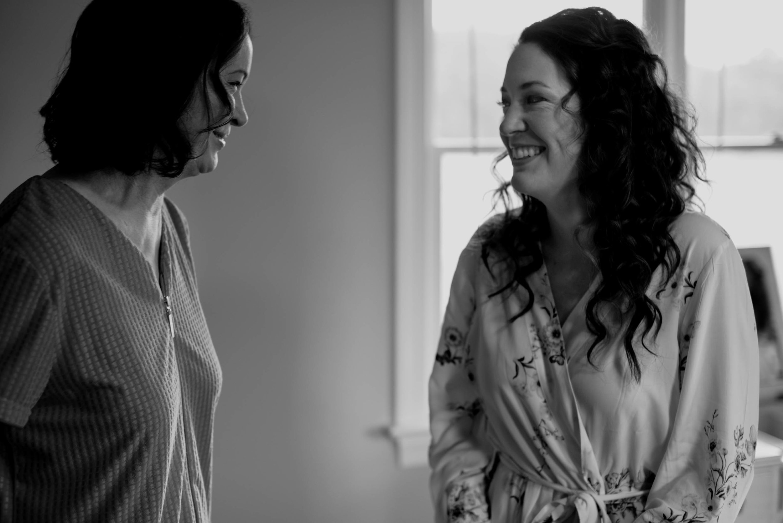 bride and her mom sharing a laugh after the brides hair and makeup were finished