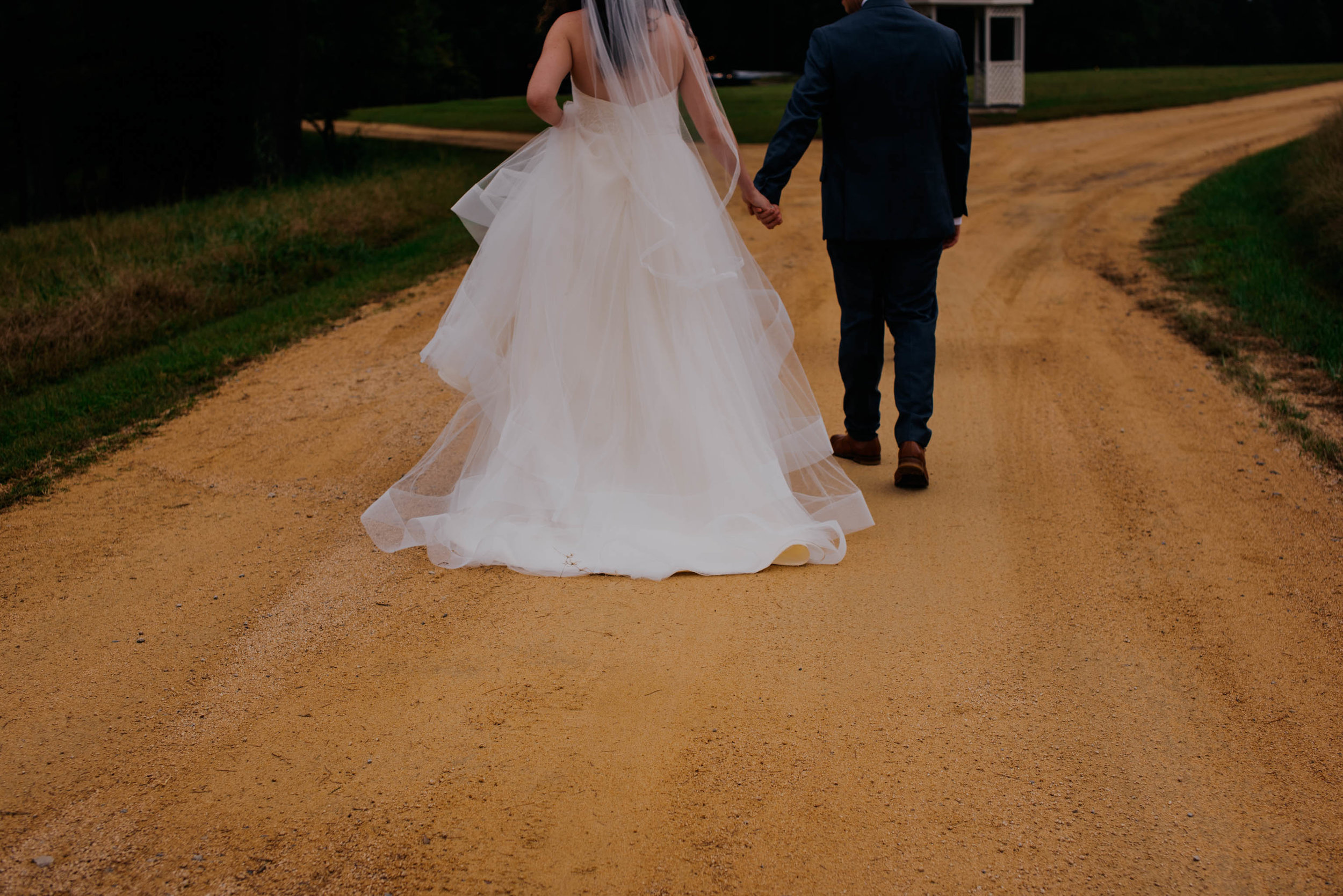 a cropped photo of the bride and groom walking down the drive of their venue to show their hands holding and the details of their wedding attire