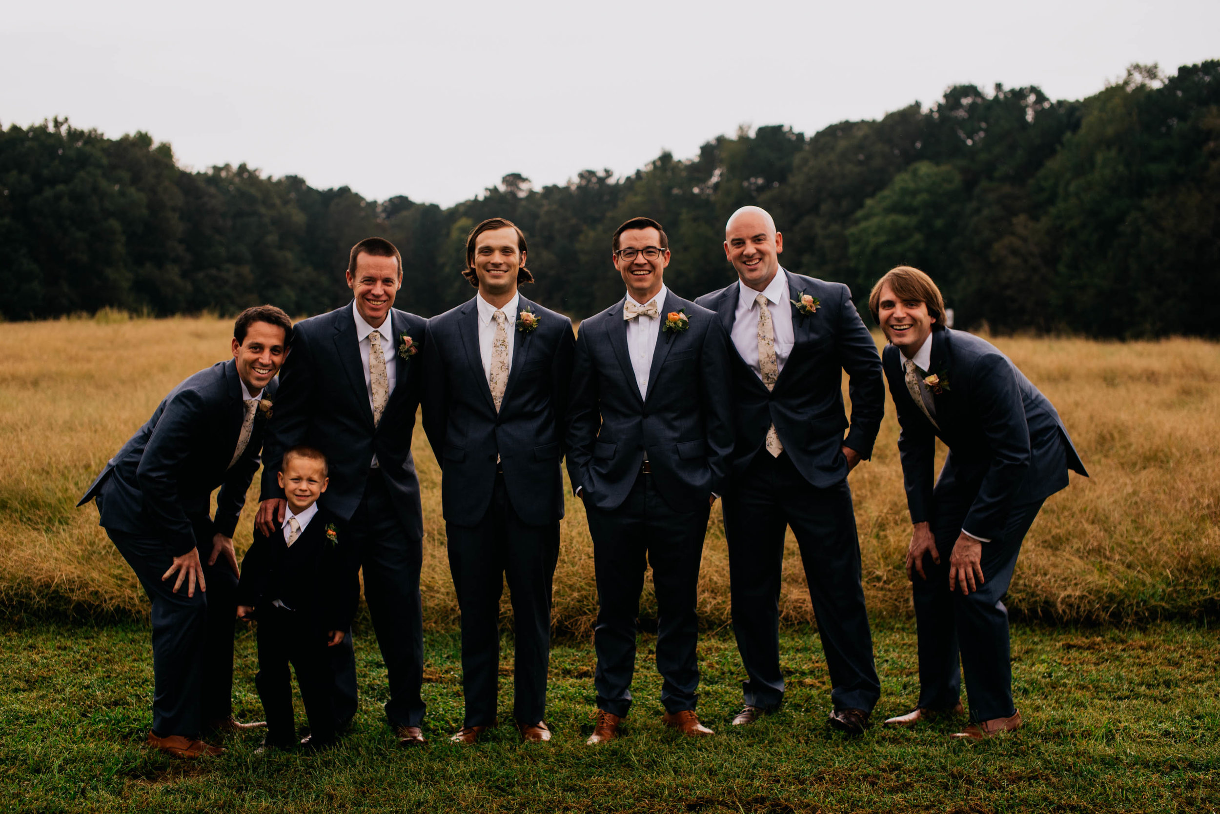 groomsmen and ring bearer posing for a photo with the fields and the woods behind them