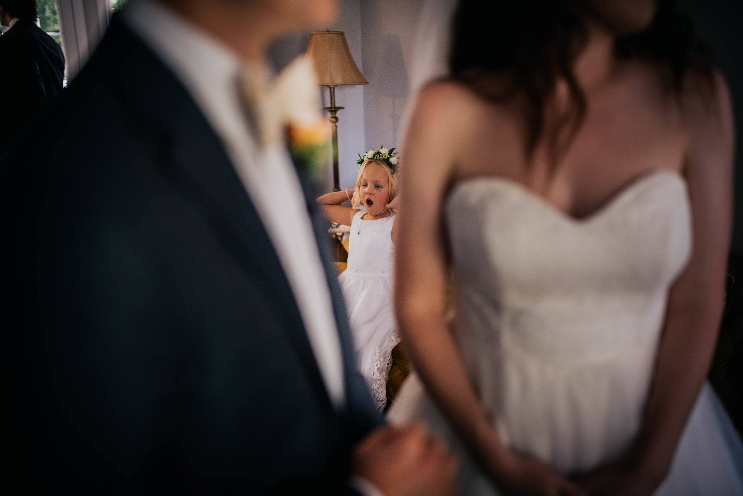 flower girl yawning in the background before the wedding ceremony
