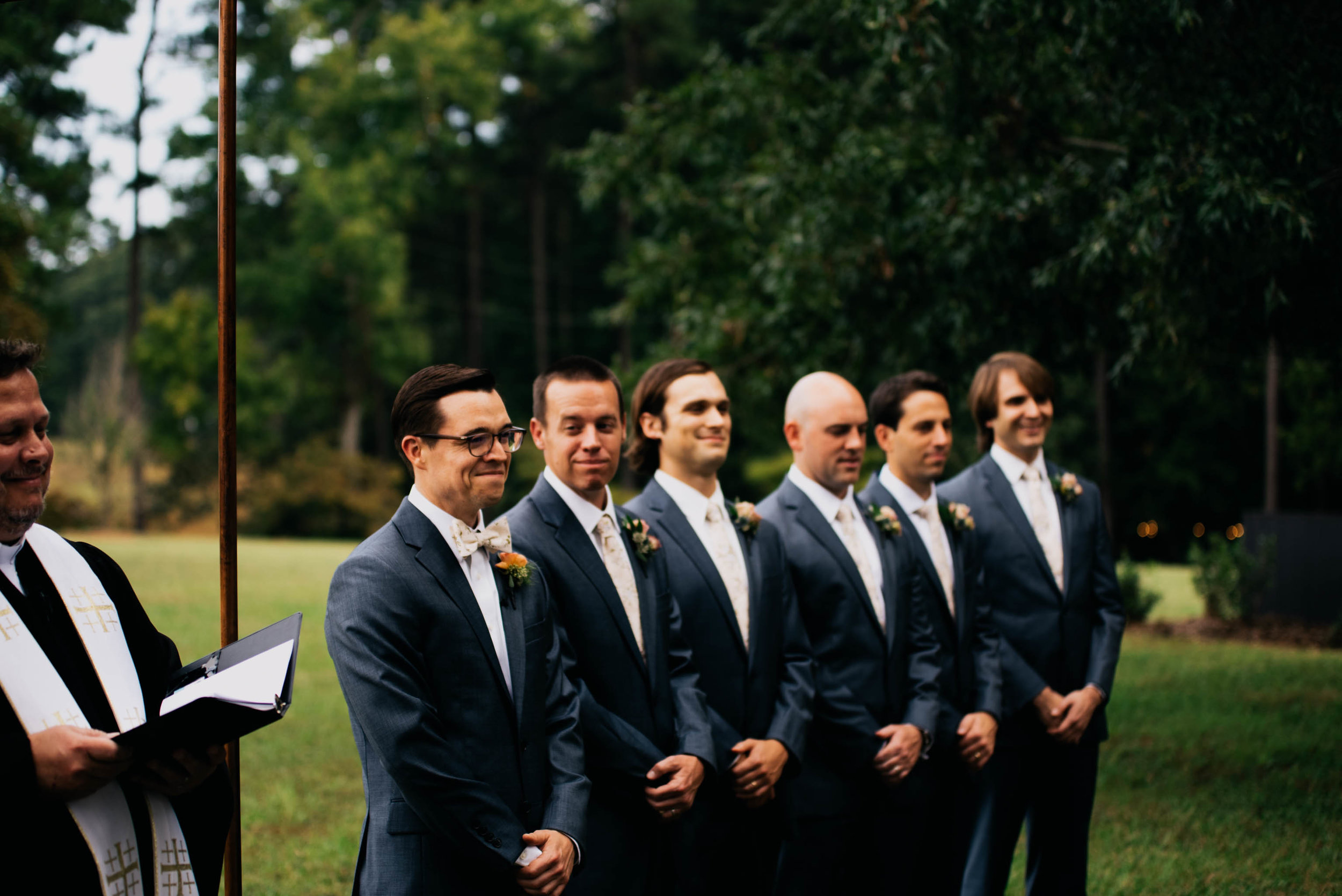 groom and his groomsmen watching the bride walk down the aisle