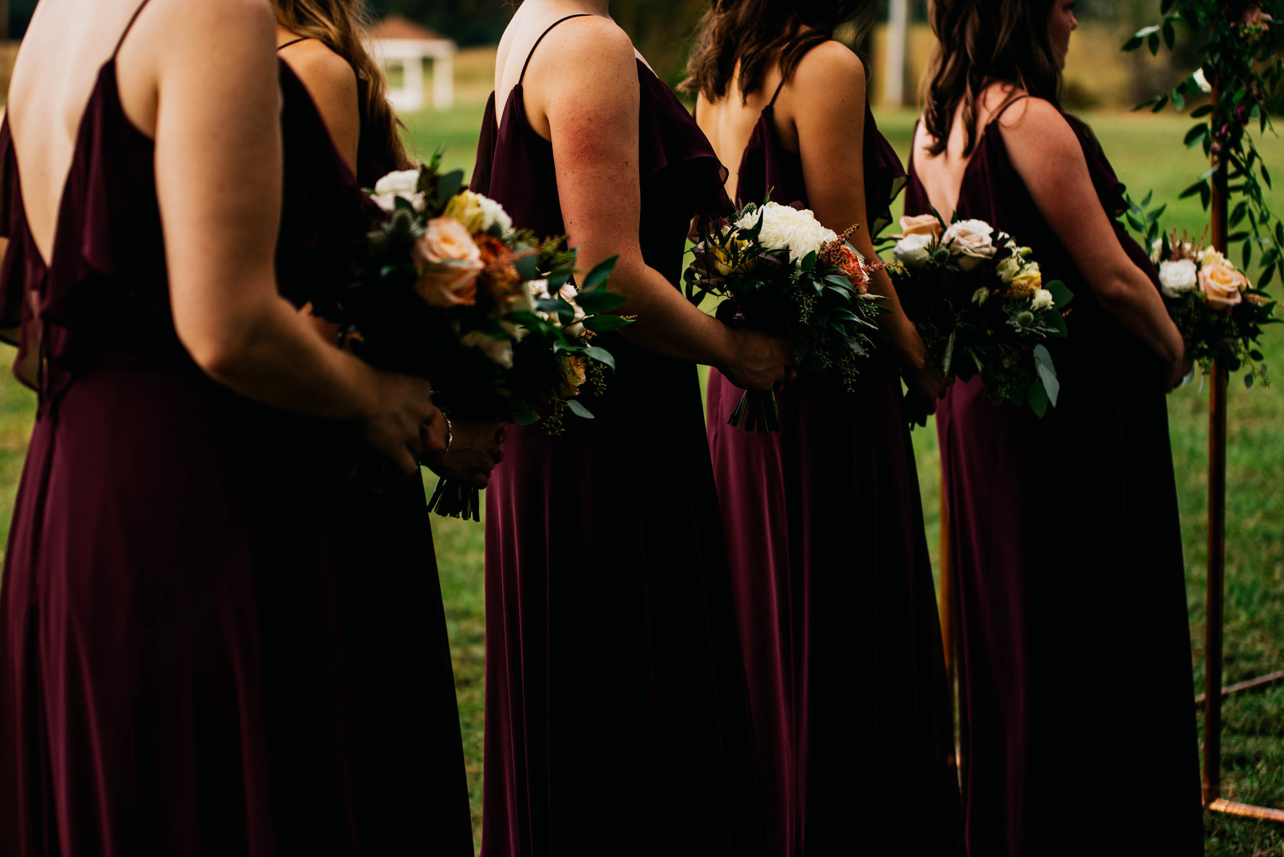 a cropped photo of the bridesmaids dresses and their florals during the wedding ceremony