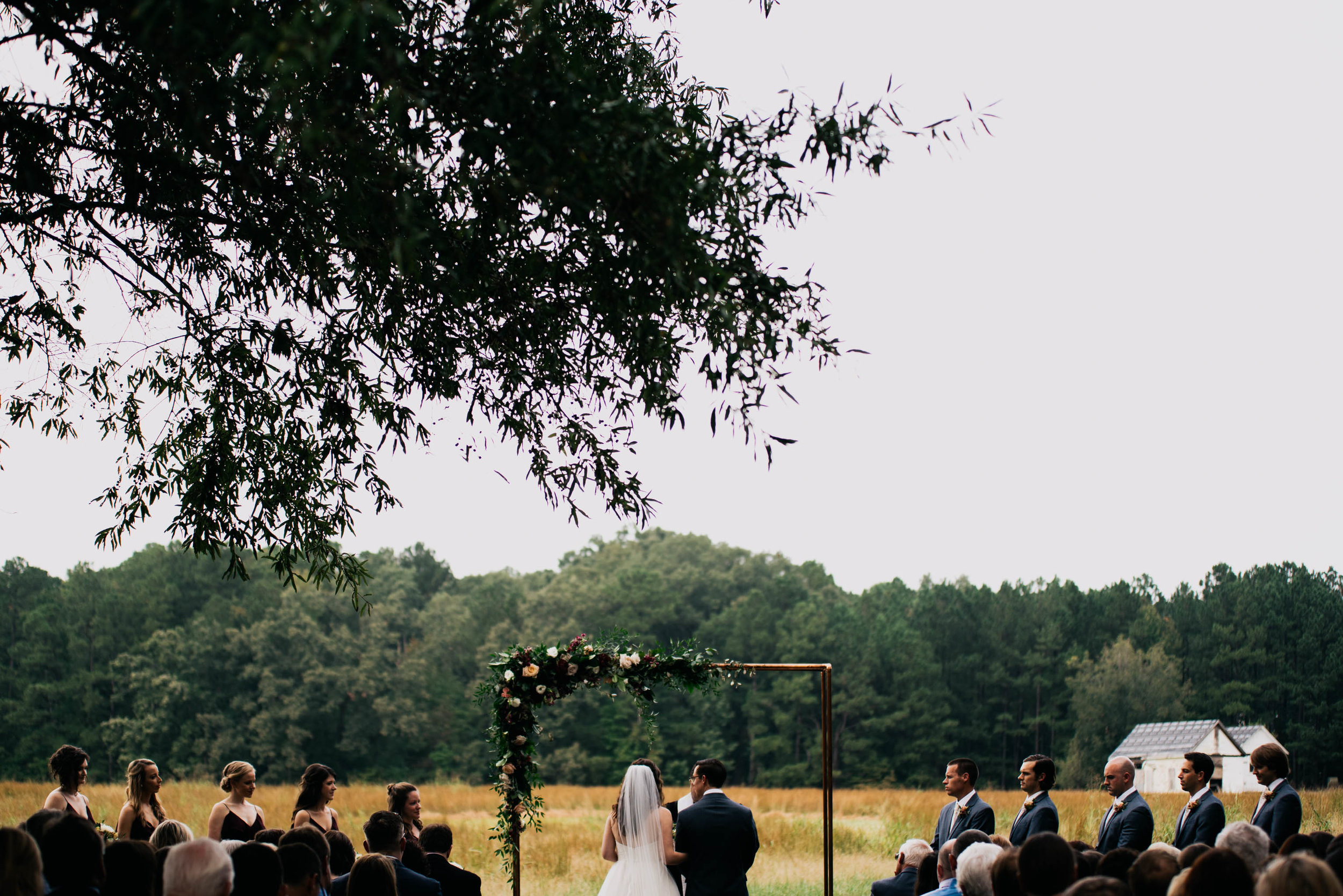 wide angle photo of the wedding ceremony as seen from the back of the ceremony space at the Meadows Raleigh
