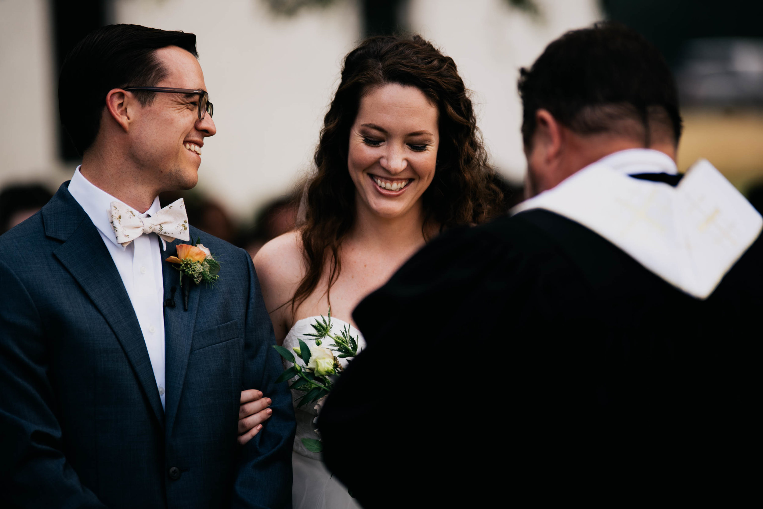 bride and groom laughing at a joke that the officiant shared during their wedding ceremony
