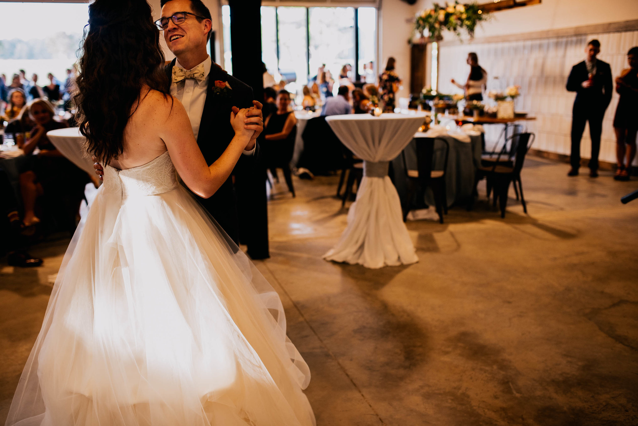 bride and groom enjoying their first dance as wedding guests look on