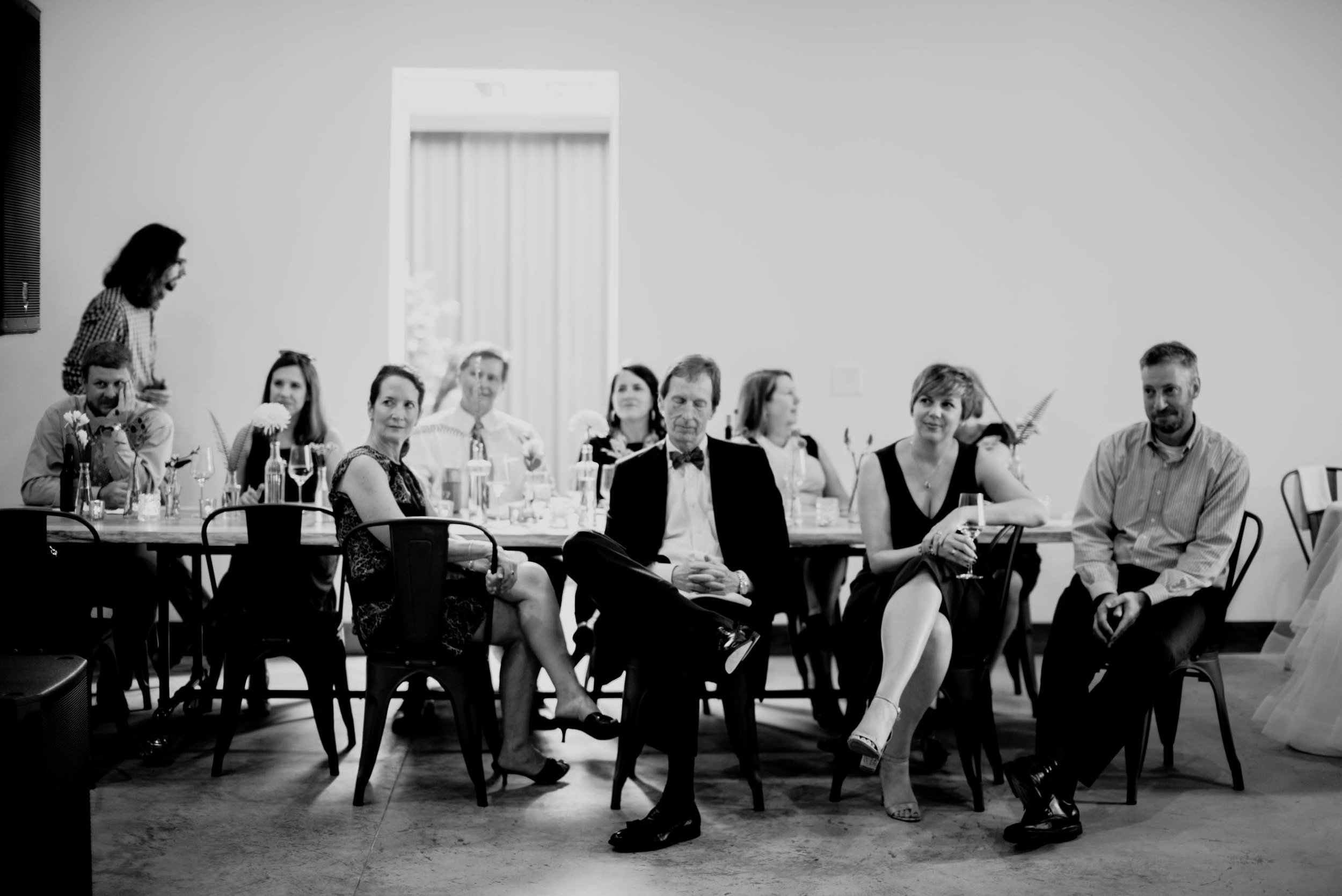 wedding guests looking on during toasts and one wedding guest asleep in his chair