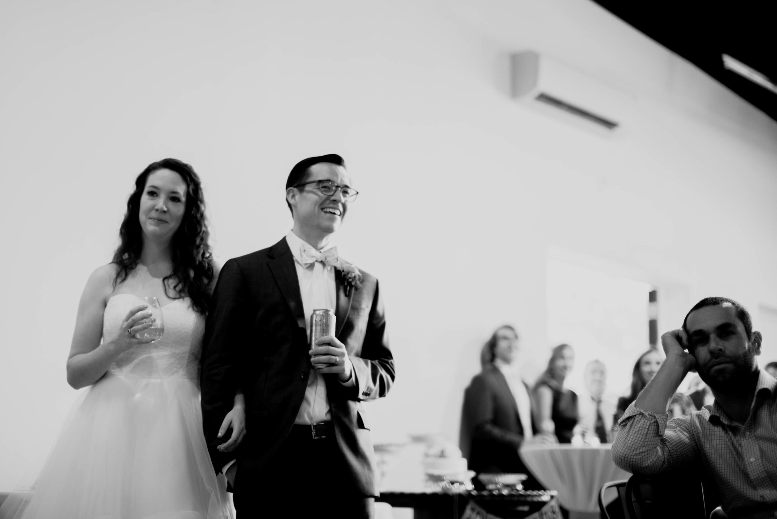 bride and groom listening to toasts during their wedding reception