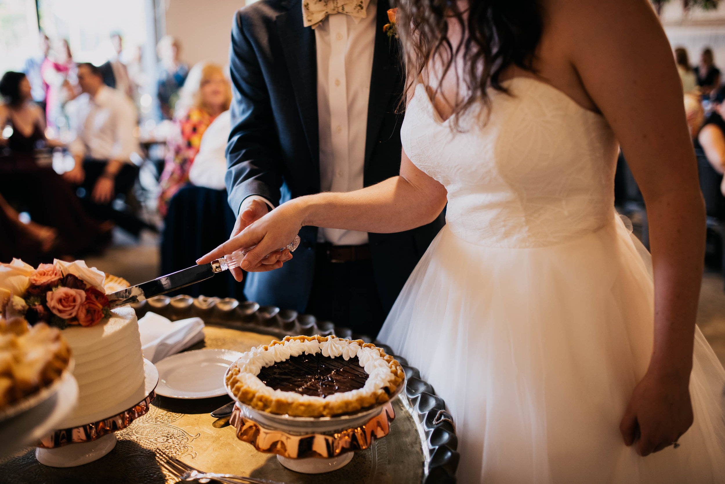 bride and groom cut the cake during their wedding reception