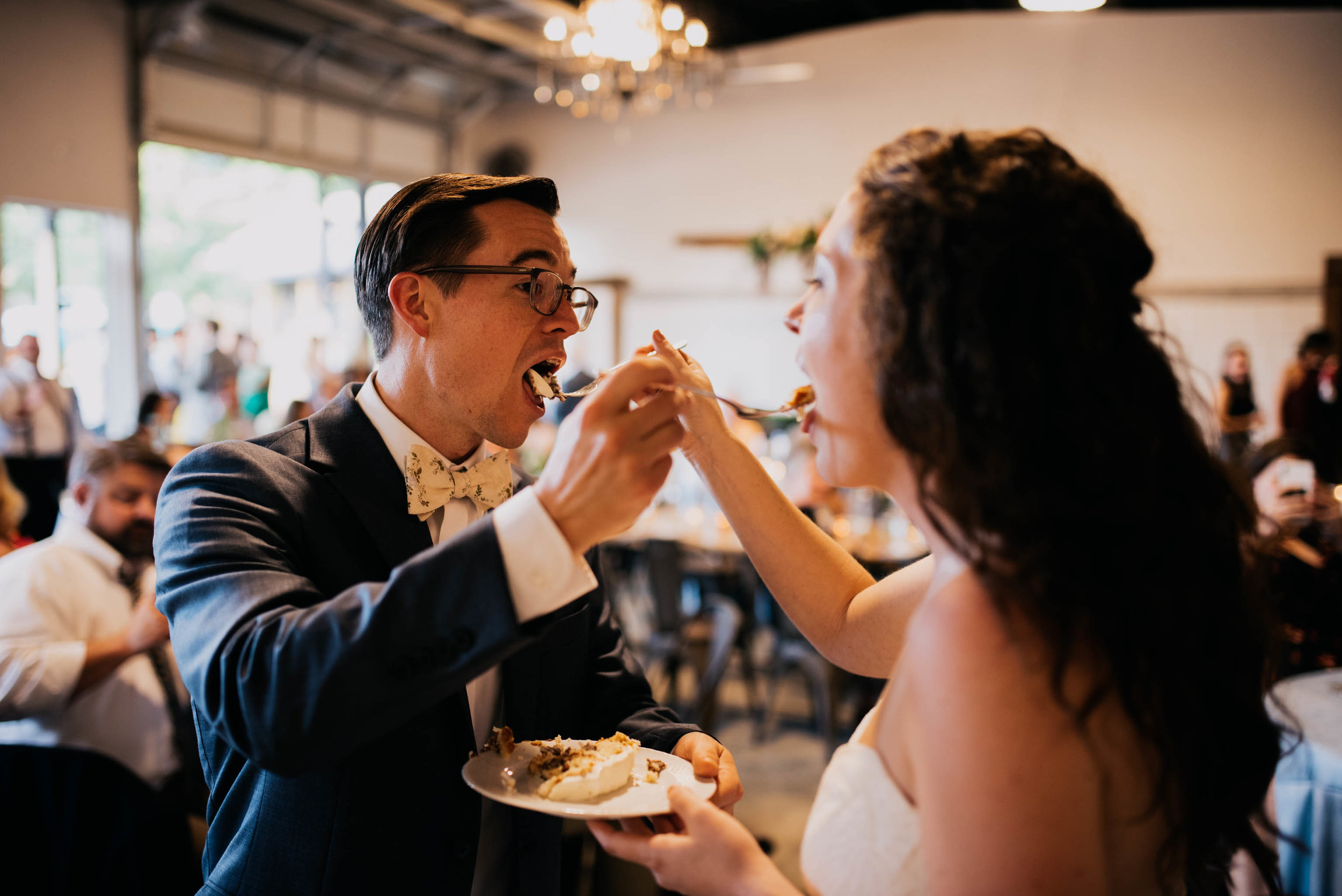 bride and groom feed each other wedding cake during their wedding ceremony