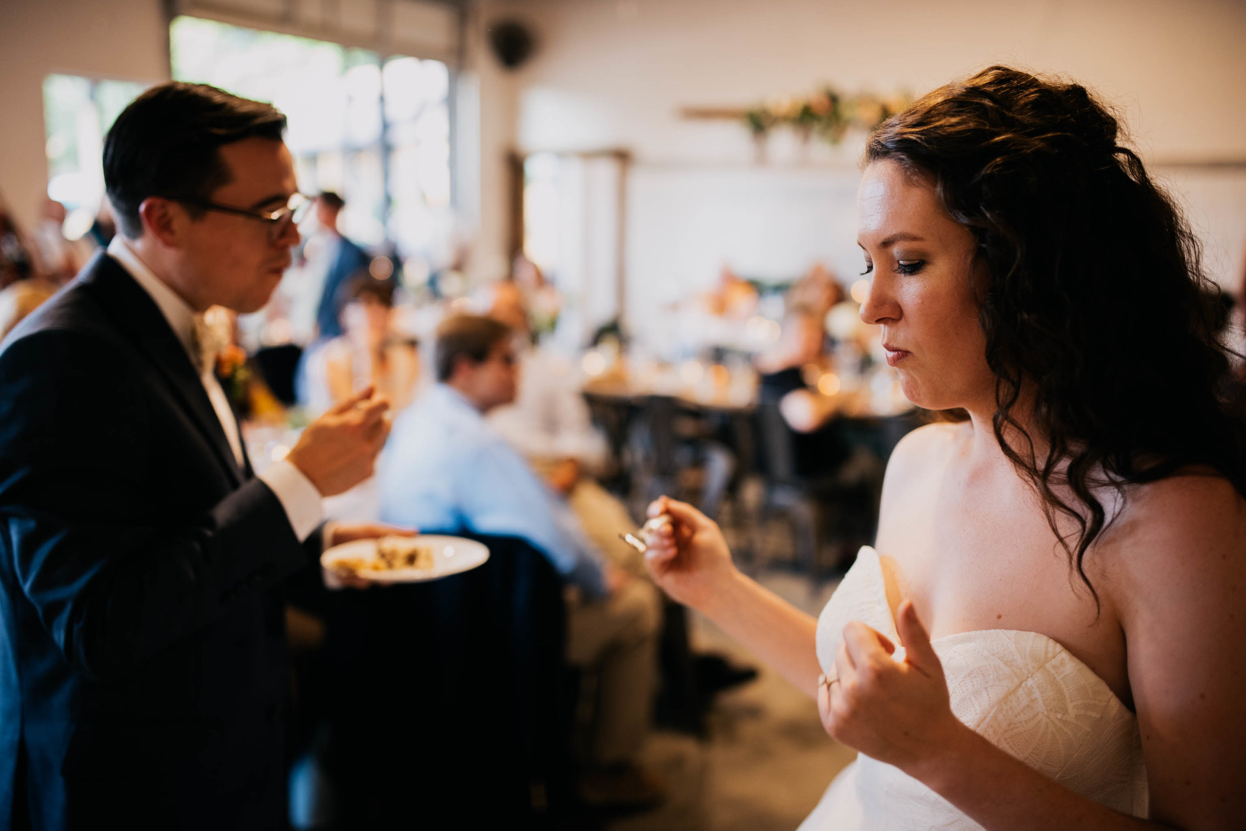bride doing a little shimmy showing her appreciation for the wedding cake