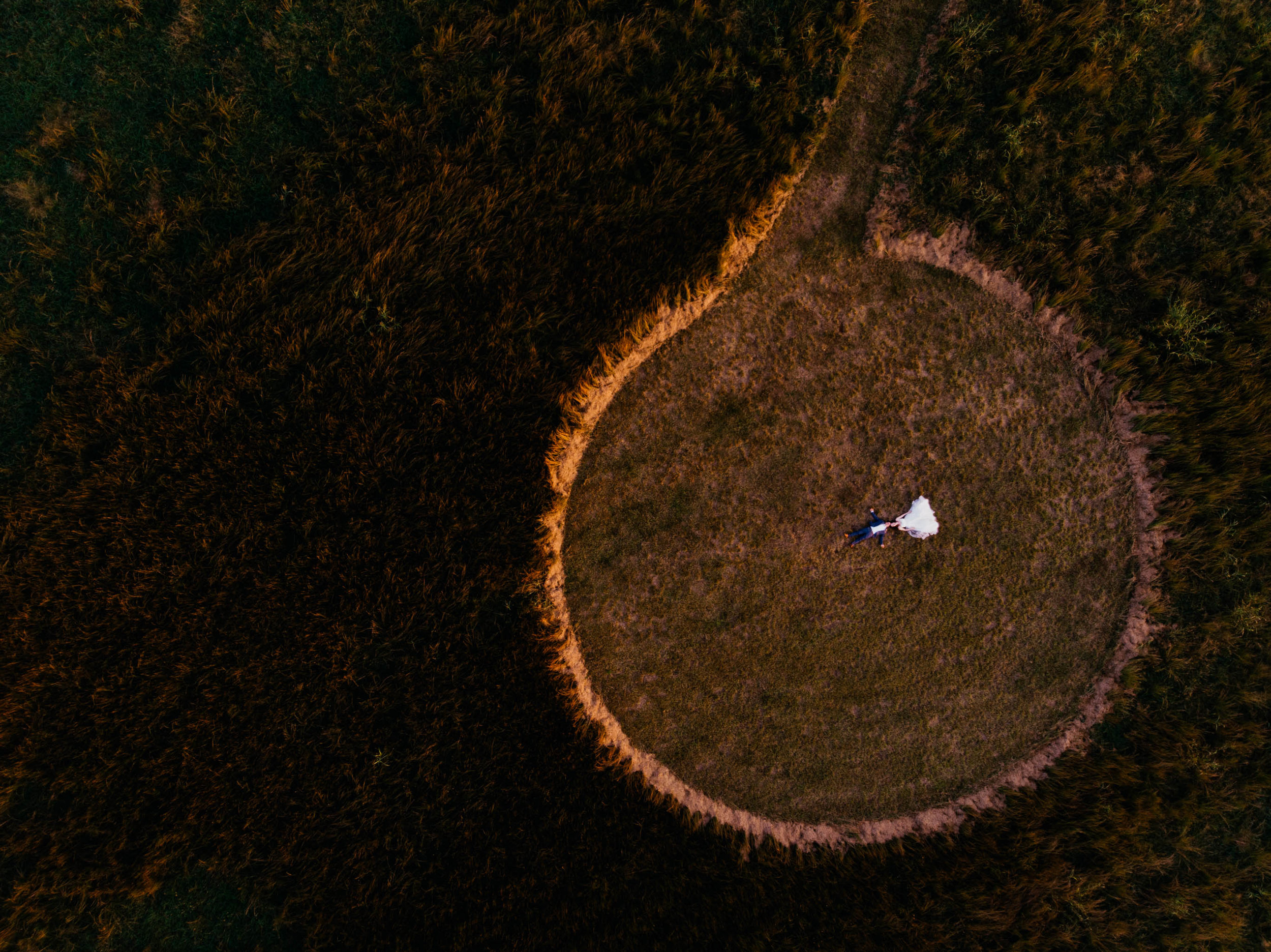 bride and groom laying in a circular cut wheat field during sunset as seen from above