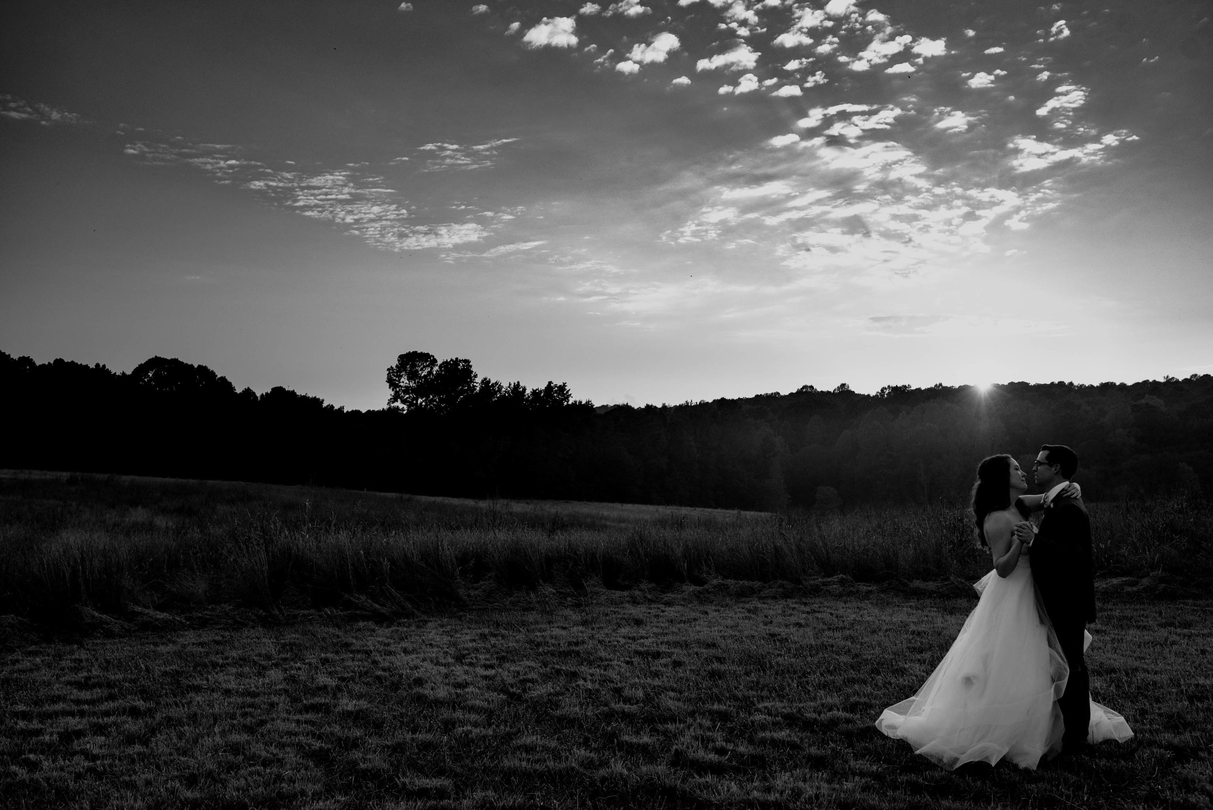 black and white photo of the bride and groom dancing in the sunset in a field during their wedding