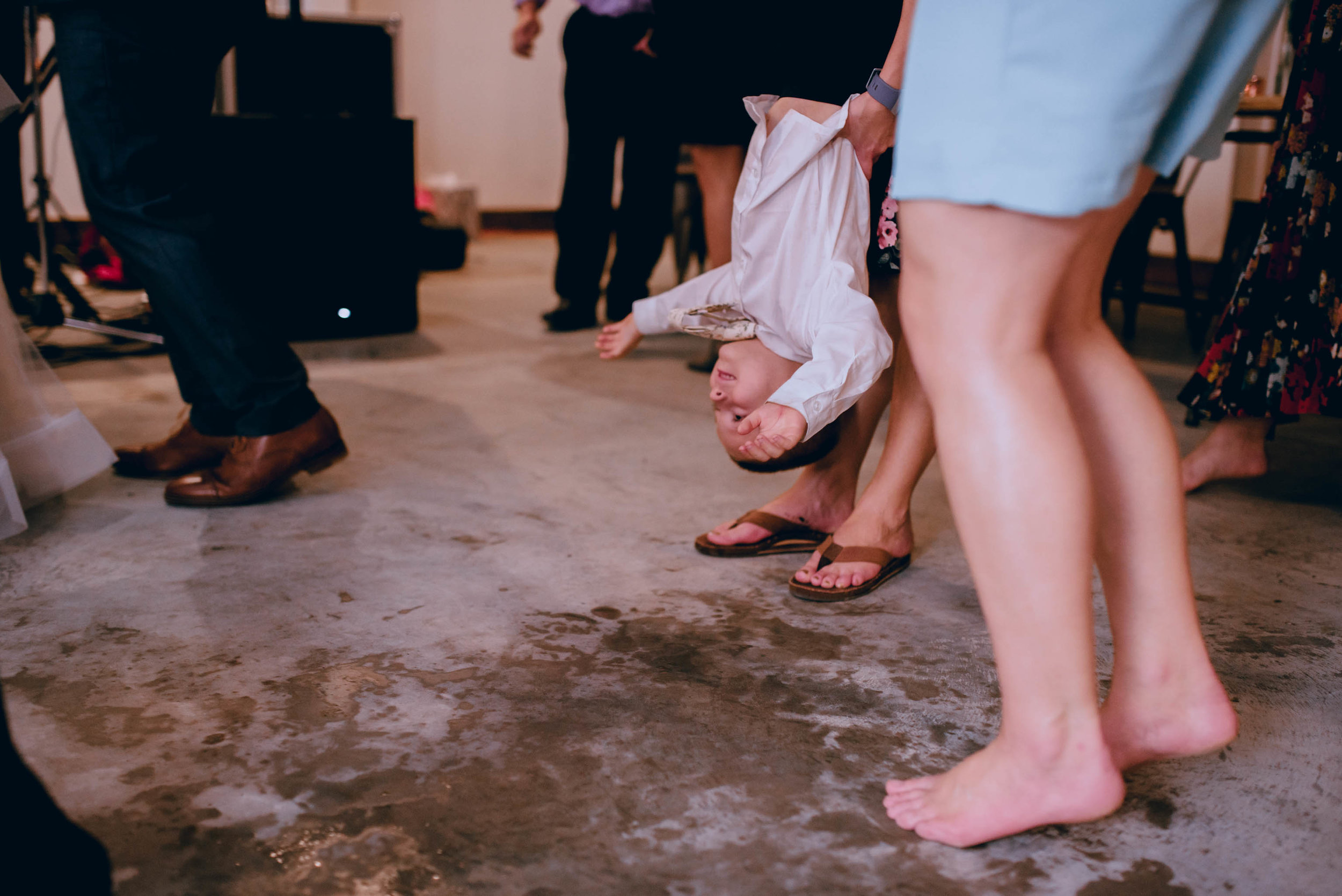 ring bearer being held upside down during dancing at wedding reception