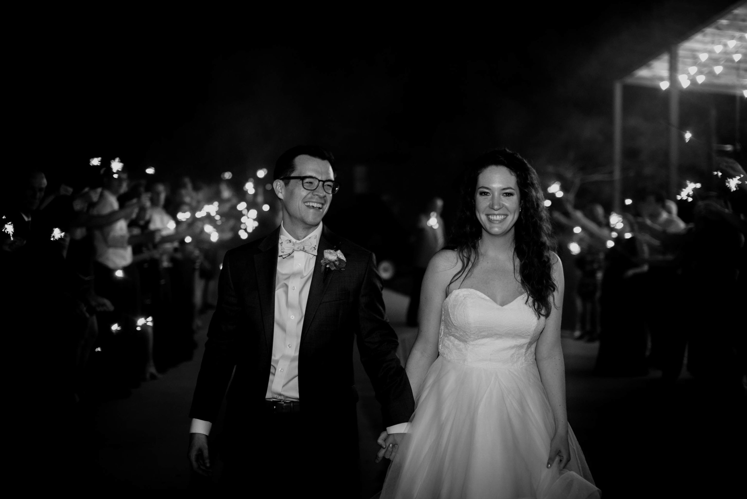 bride and groom smiling wide as they exit their wedding night
