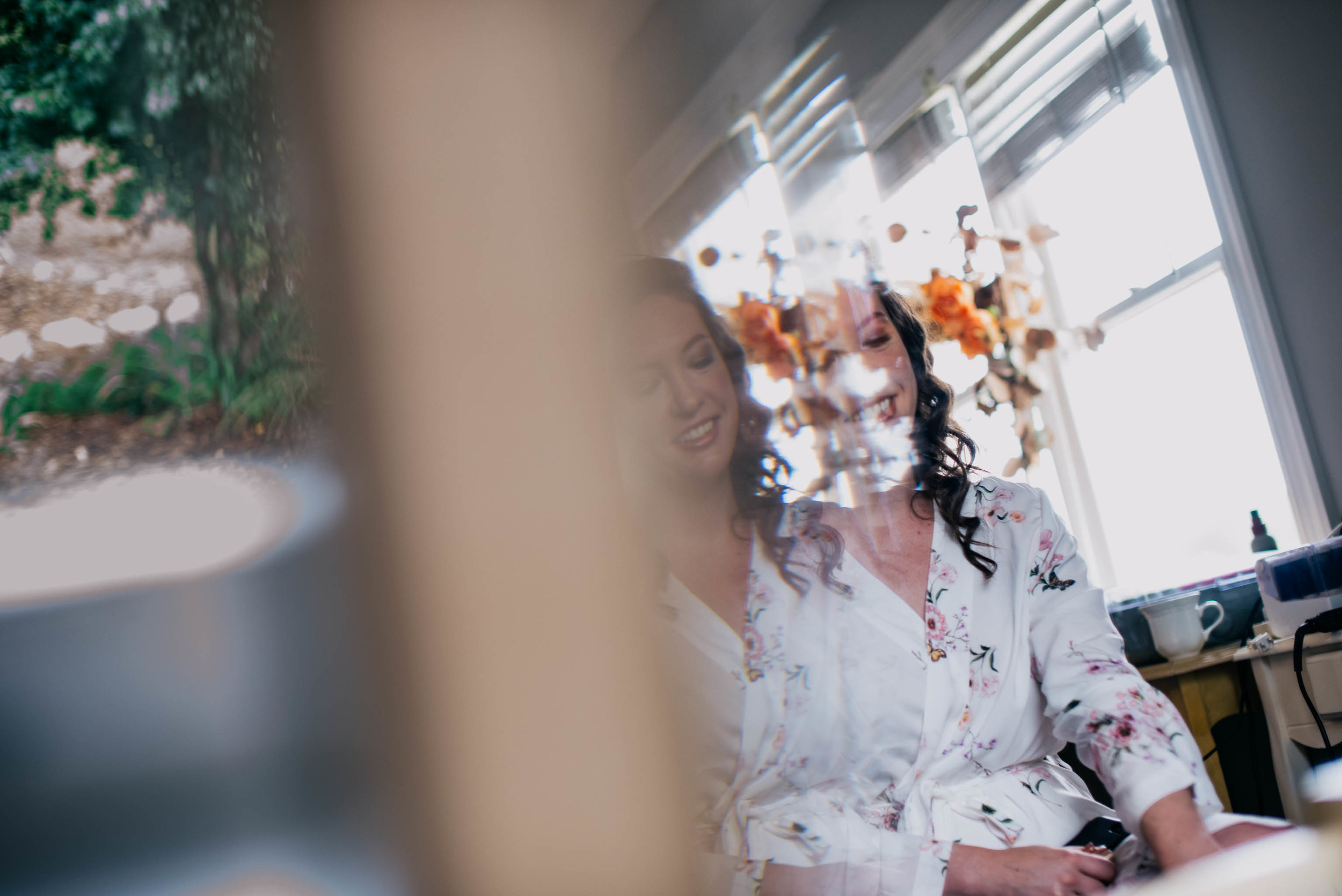 reflection of bride as she finishes up her hair and makeup