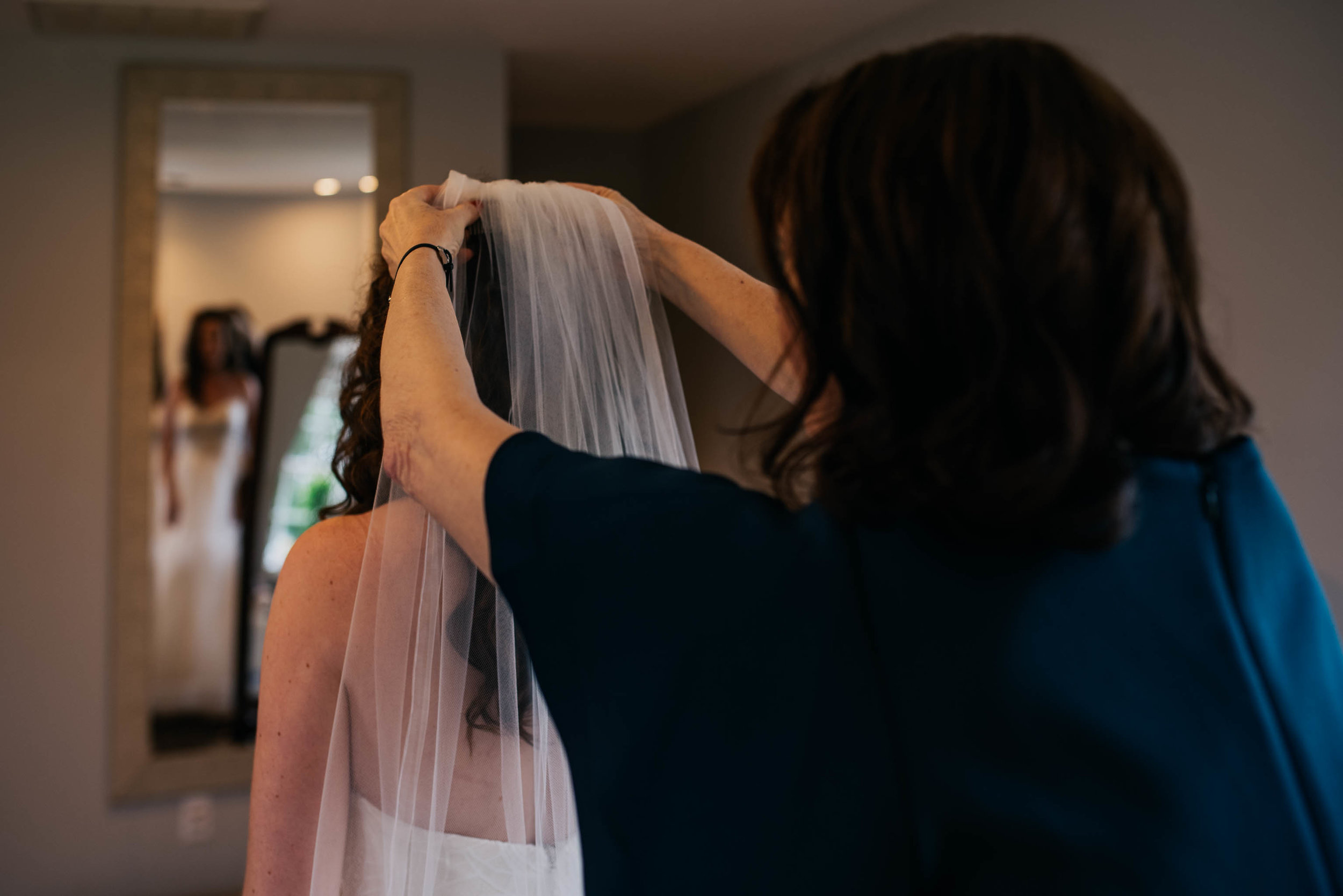 mother of the bride fixes the brides veil in place