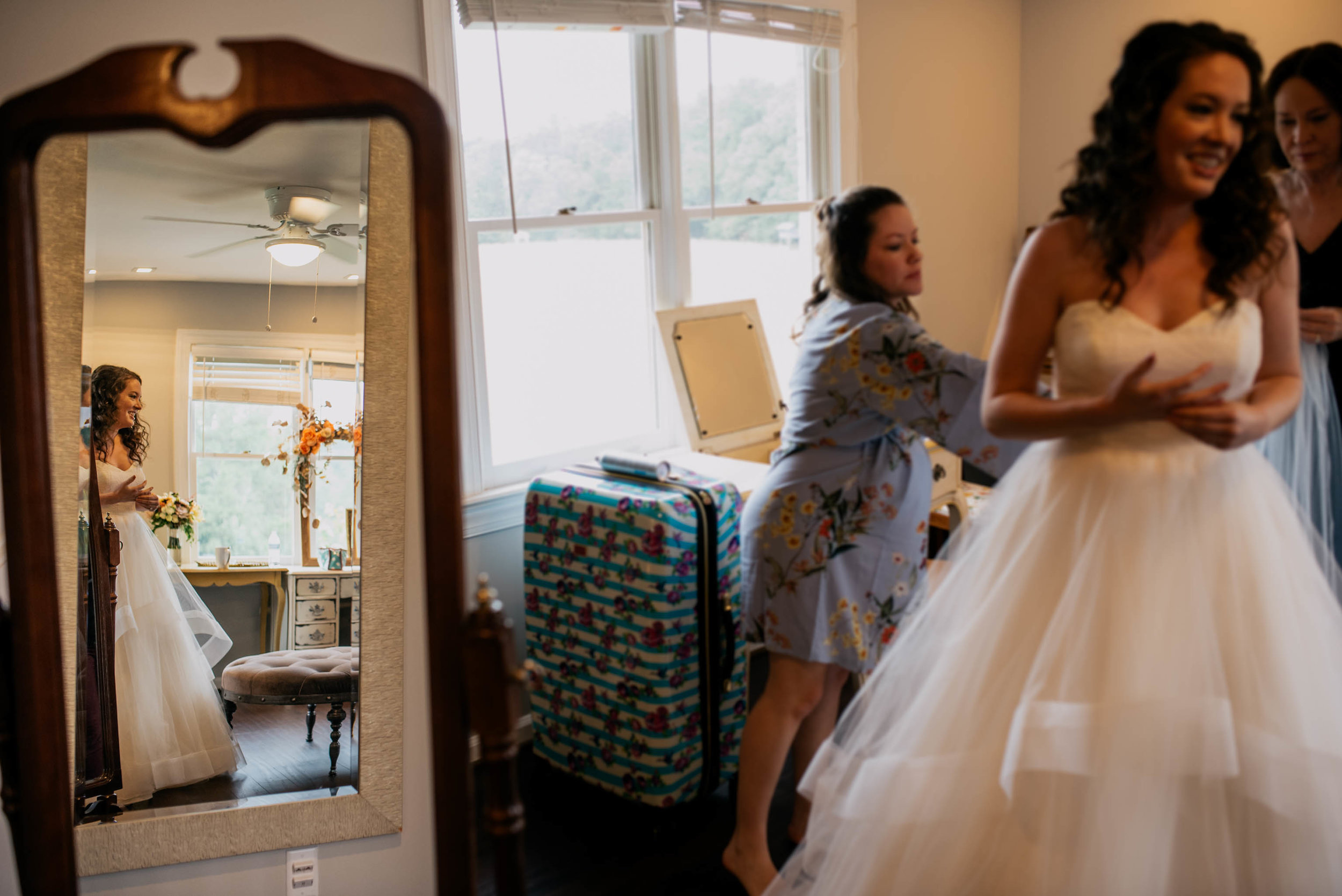 reflection of bride as she finished getting on her dress while her bridesmaids look on