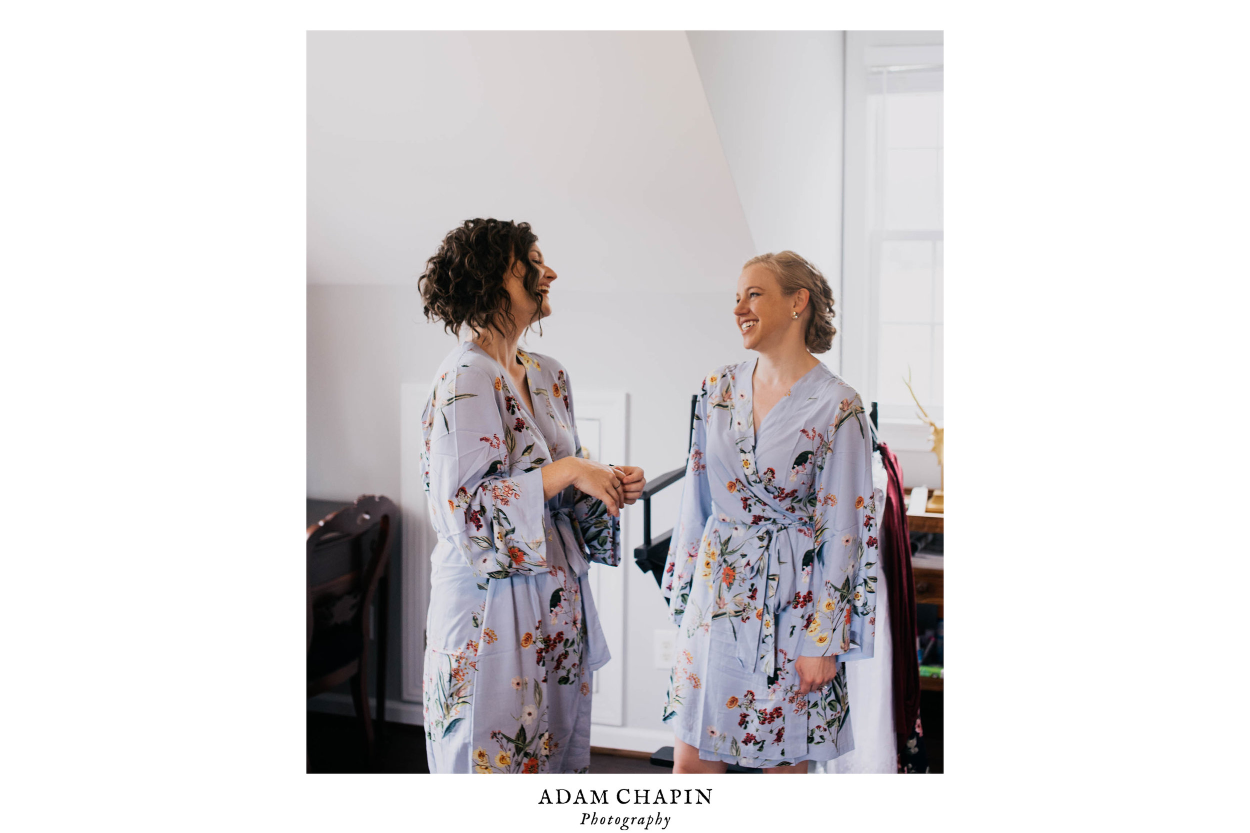 two of the bridesmaids laughing as they get ready for the wedding day