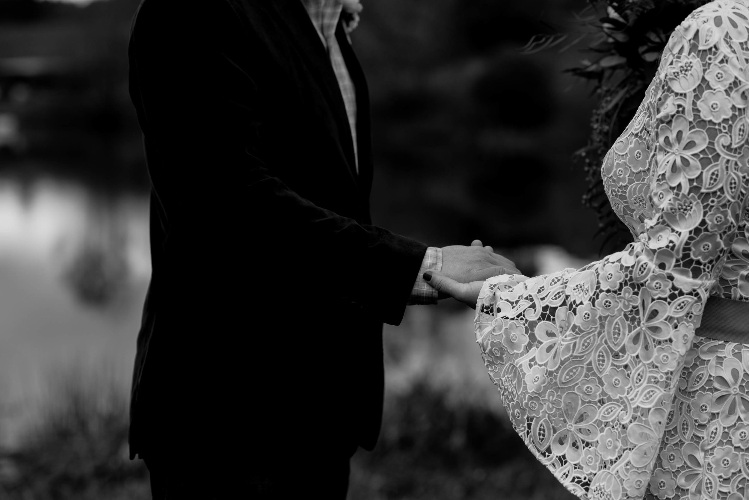 black and white photograph of bride and groom holding hands