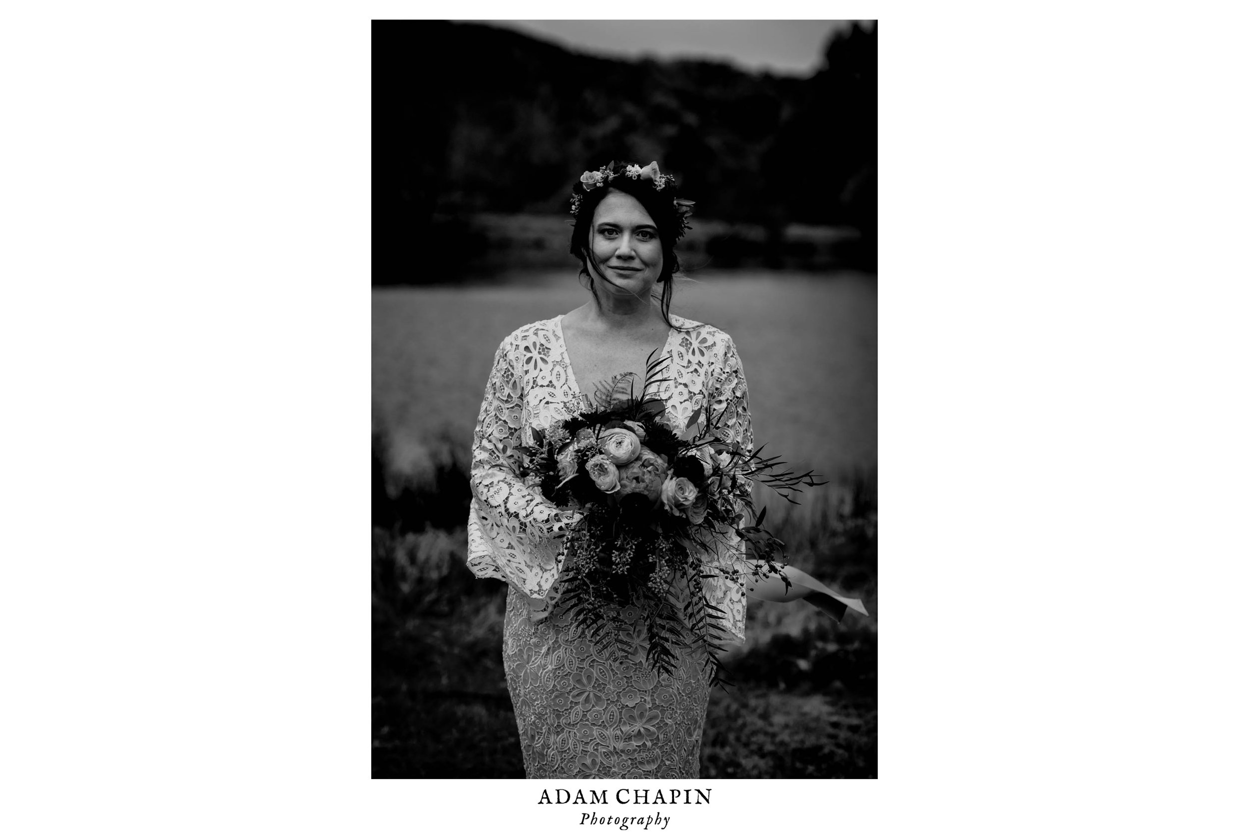 black and white photograph of bride holding her bouquet as the wind sweeps her hair across her face