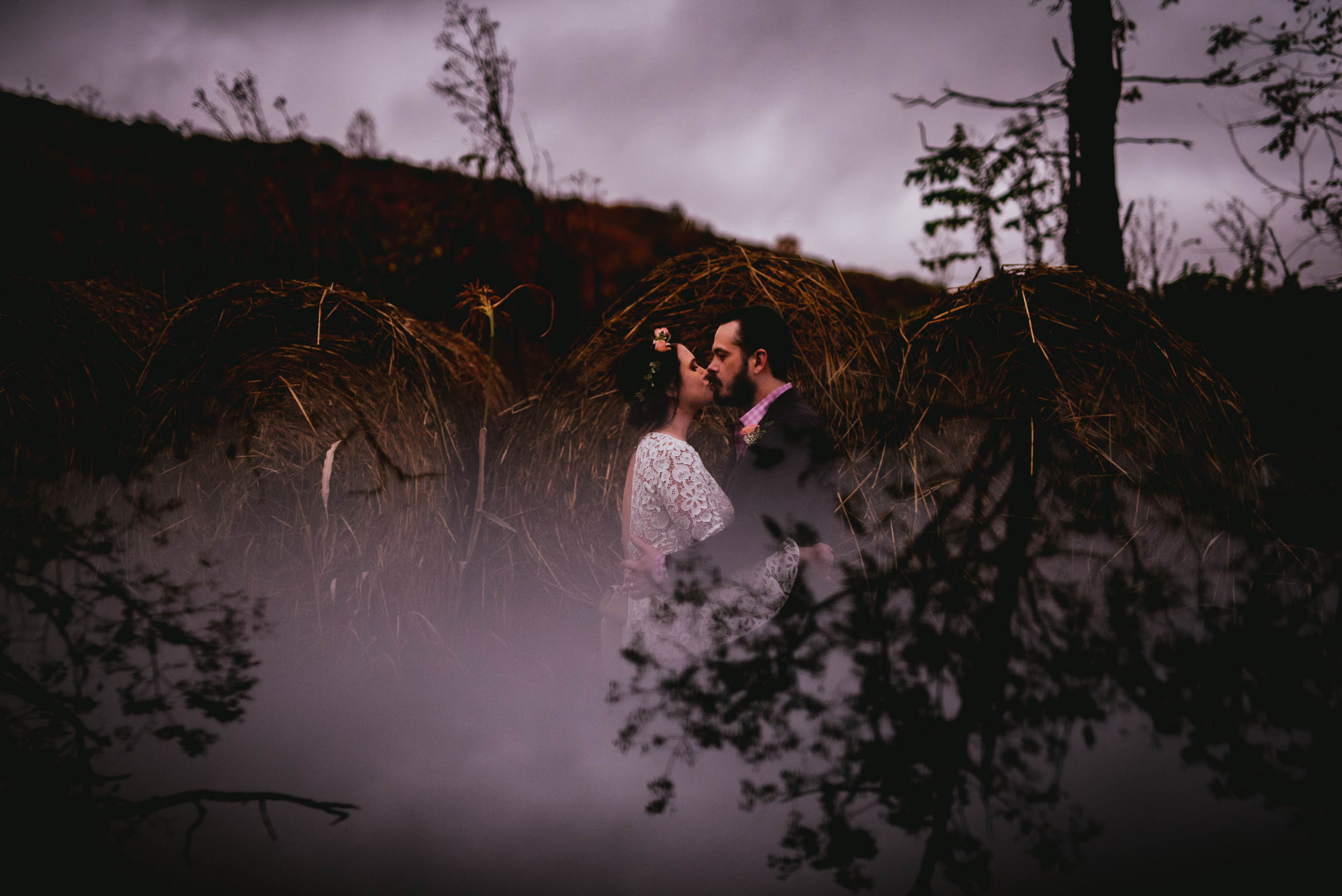 bride and groom kissing in front of the hay bails with the trees reflected beneath them