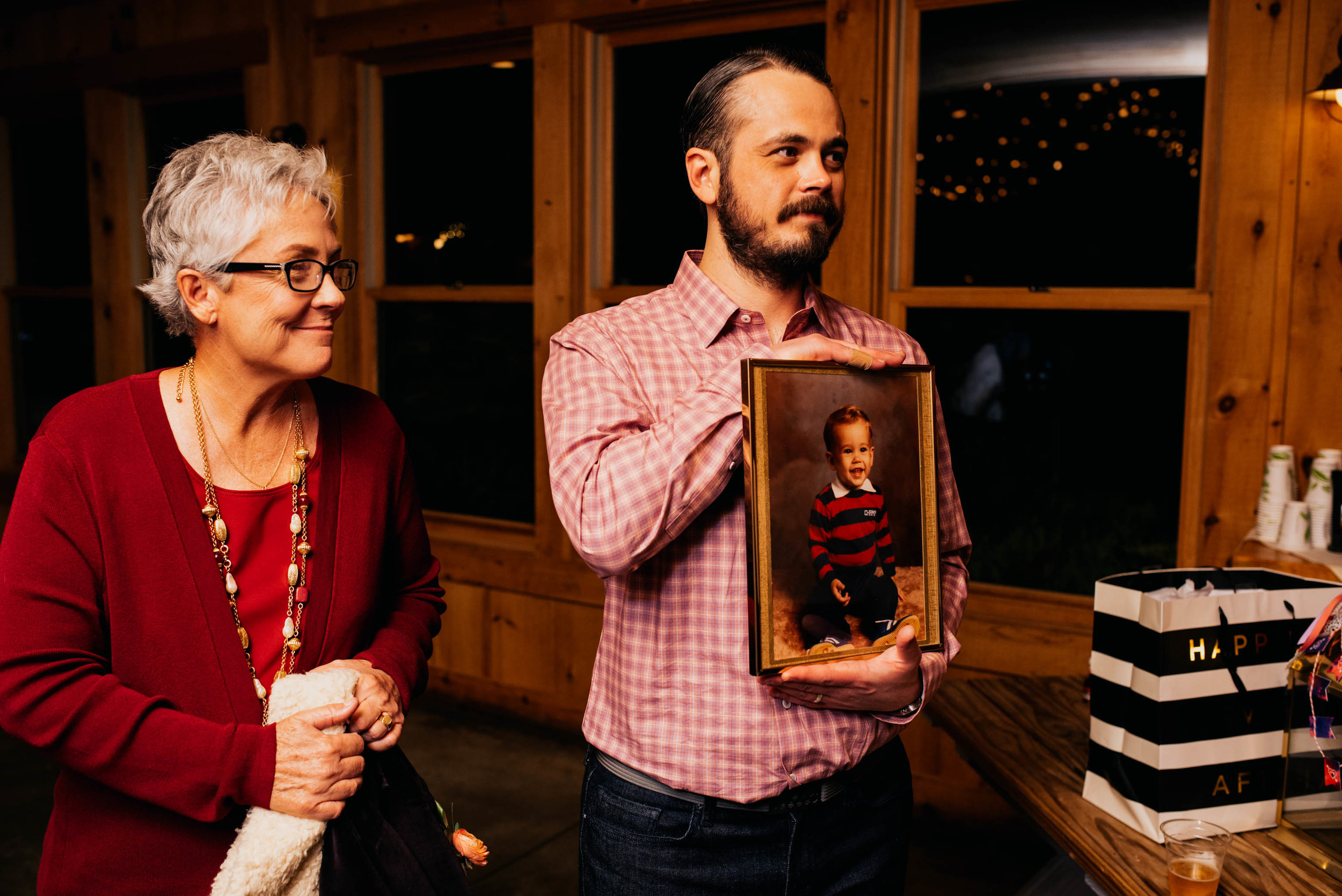 groom holding up a wedding gift of a portrait of himself as a kid