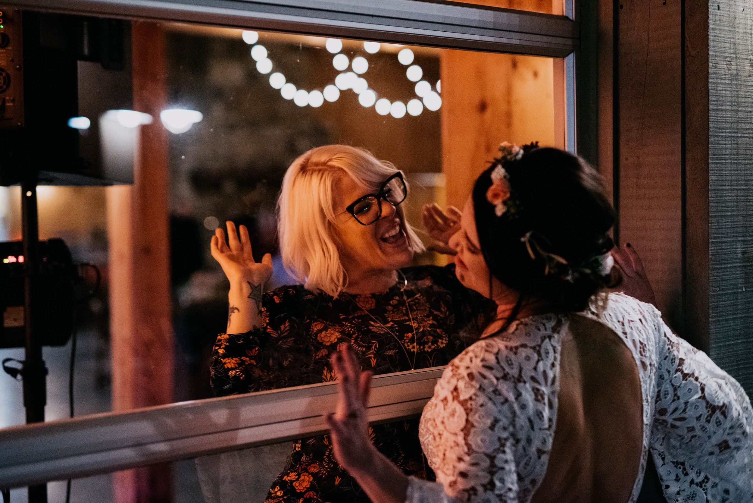 bride and her friend dancing on either side of the window
