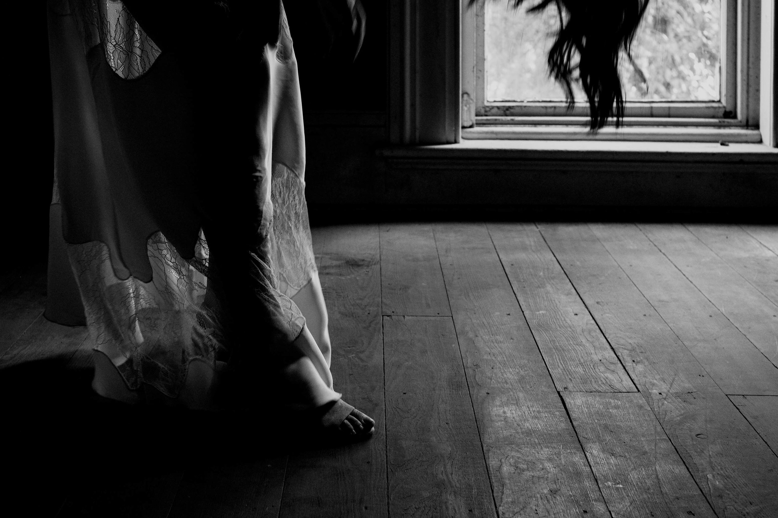 Black and white photo of bride getting into her shoes