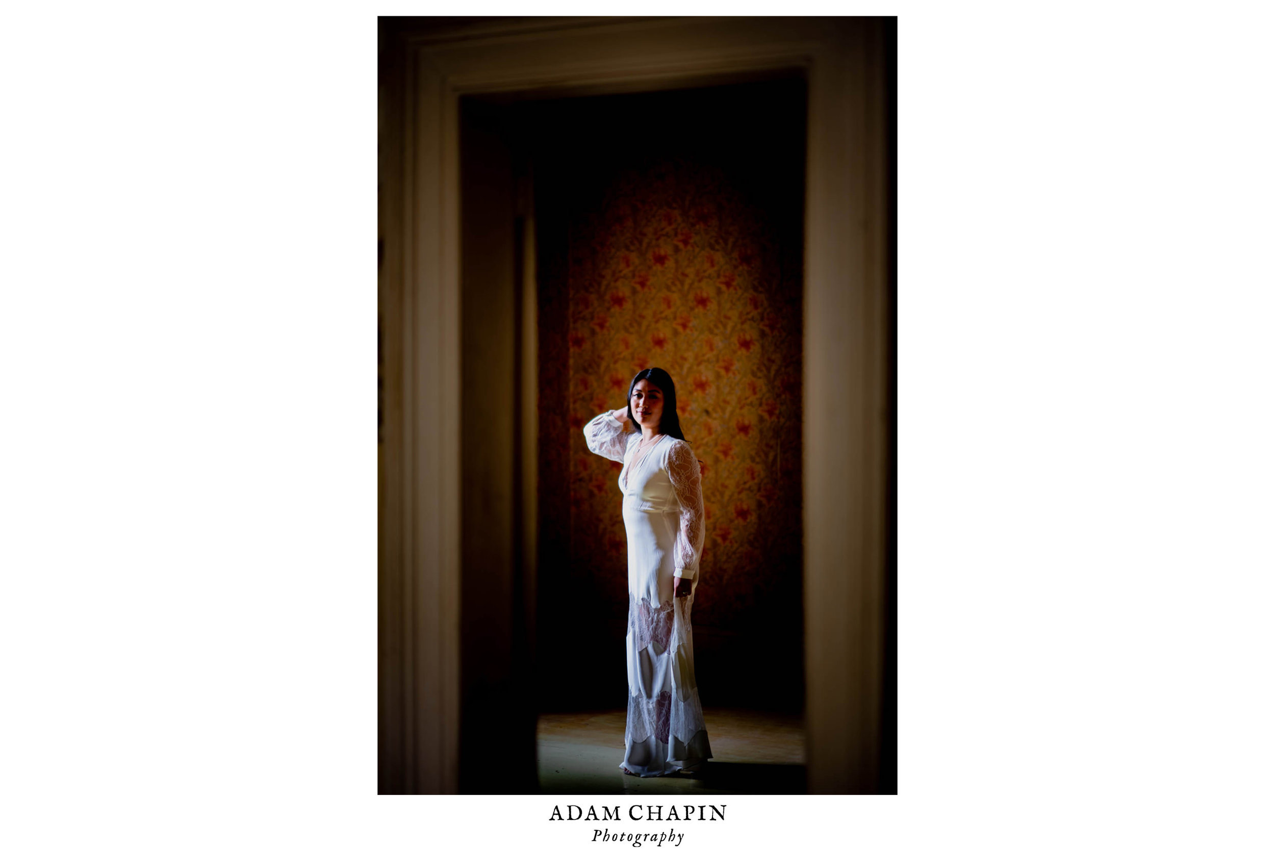 Bride framed by a doorway as she stands in an empty room with ornate wallpaper behind her