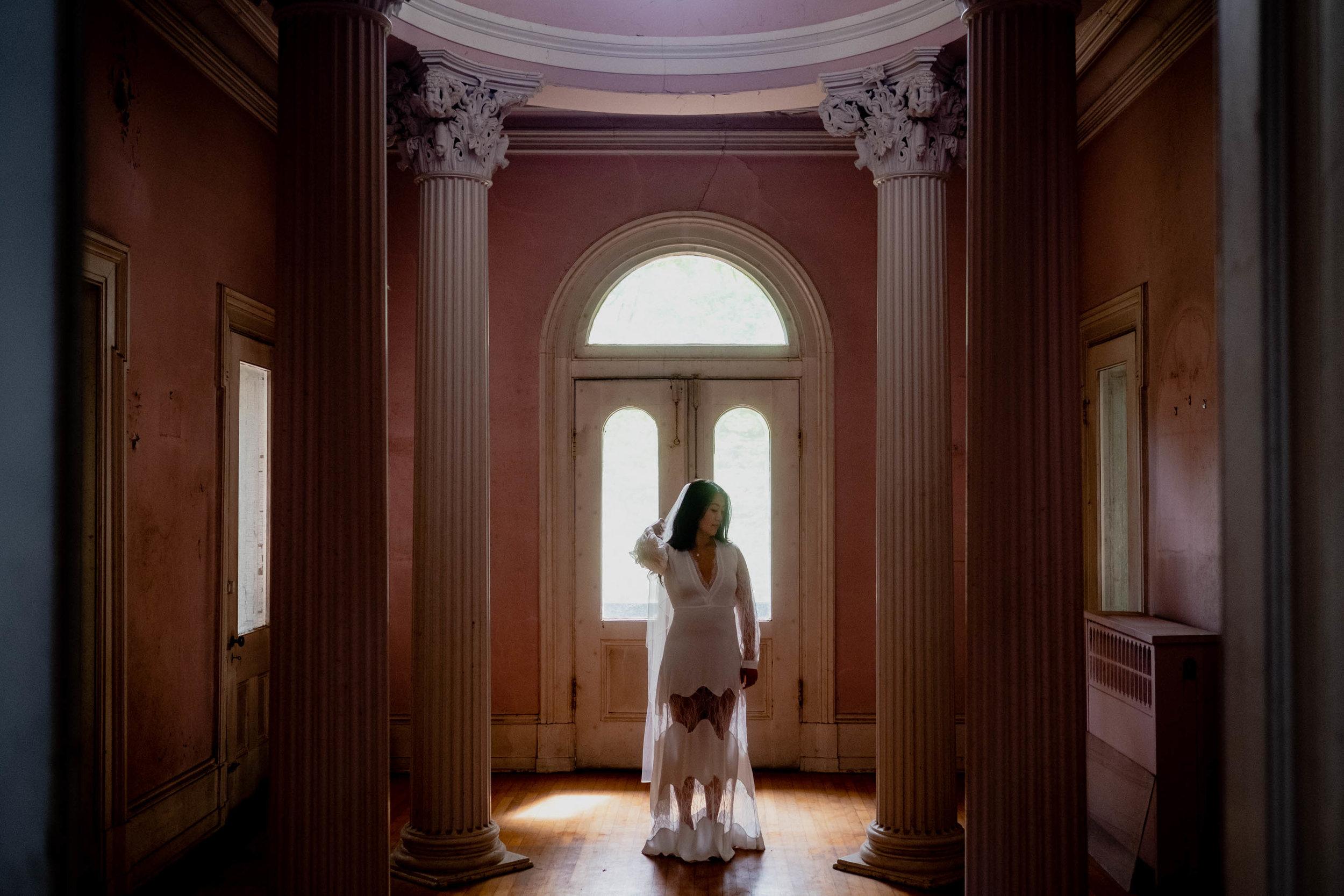 Bride standing in front of front door light at Montfort House in Raleigh NC