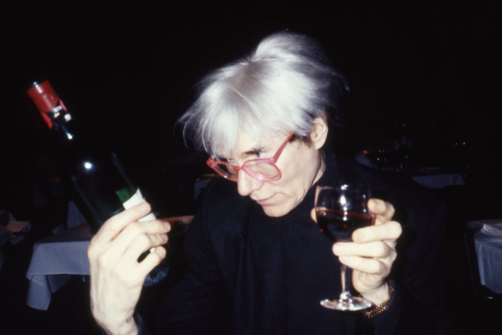 Andy Warhol with a glass of red circa 1985. This photo was taken by Paige Powell and is ©Paige Powell. Any reproduction of this photograph is strictly prohibited without the express permission of Paige Powell Archive