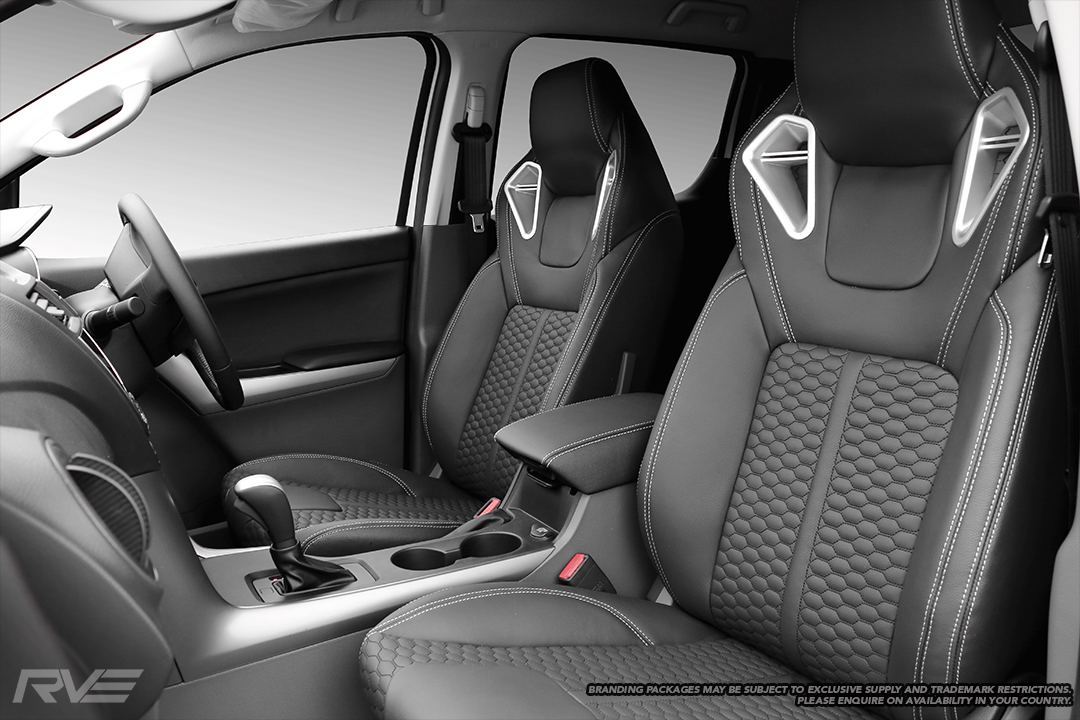 Upgraded Monza sport seats in OEM spec black leather with silver stitching and black-stitched honeycomb inserts.