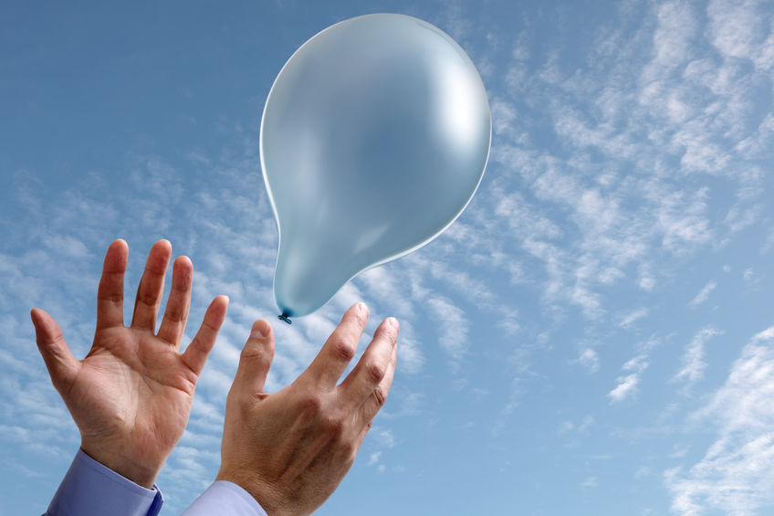 25355852 - releasing a balloon into the air concept for dreams and aspirations with copy space on the balloon and sky