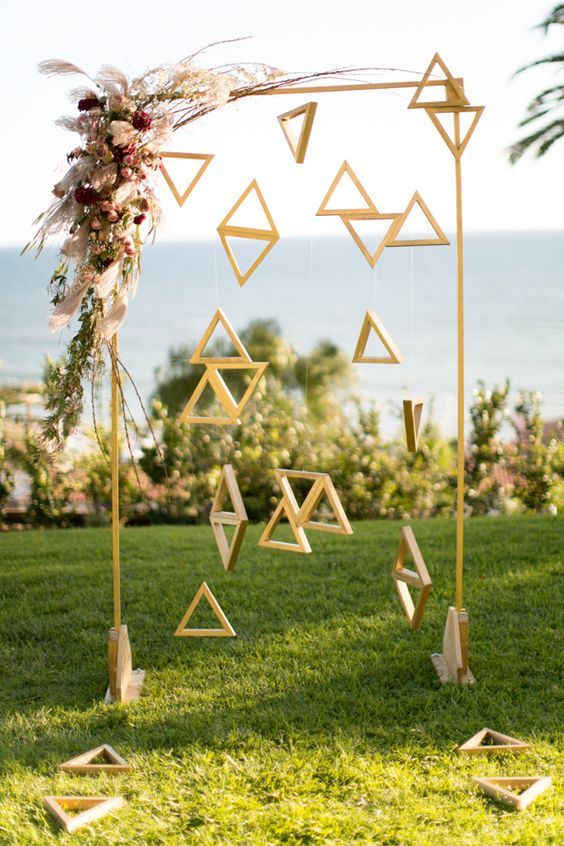 13-an-arch-with-wooden-triangles-hanging-and-bold-flowers-on-the-corner.jpg